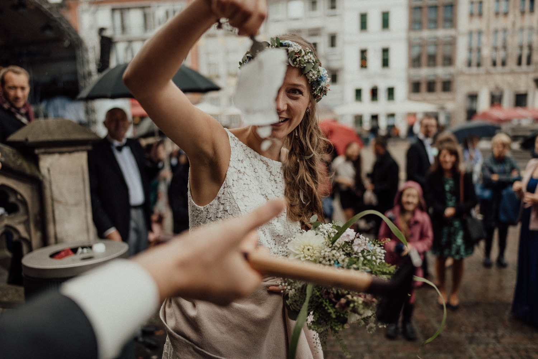Glückliche Braut hat Schlüssel aus Eisklotz geschlagen vor weißem Saal Aachen