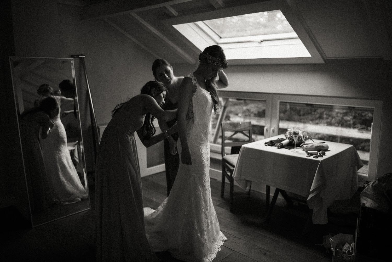 Die Brautjungfern helfen der wunderschönen Braut in ihr fabelhaftes Brautkleid für die bevorstehende freie Trauung im Wald nahe dem Lua Pauline, Aachen