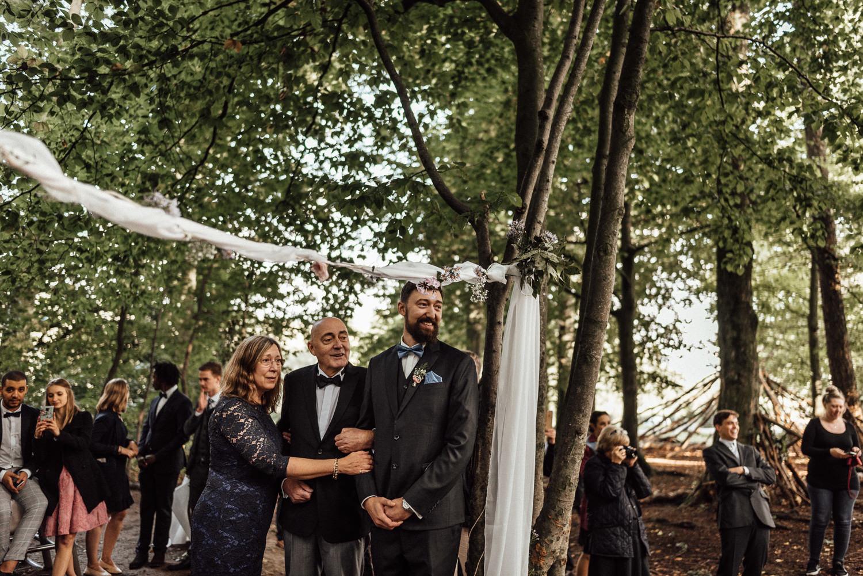 Gerührter Bräutigam mit seinen Eltern bei Anbetracht seiner wunderschönen Braut bei der freien Waldhochzeit nahe Köln