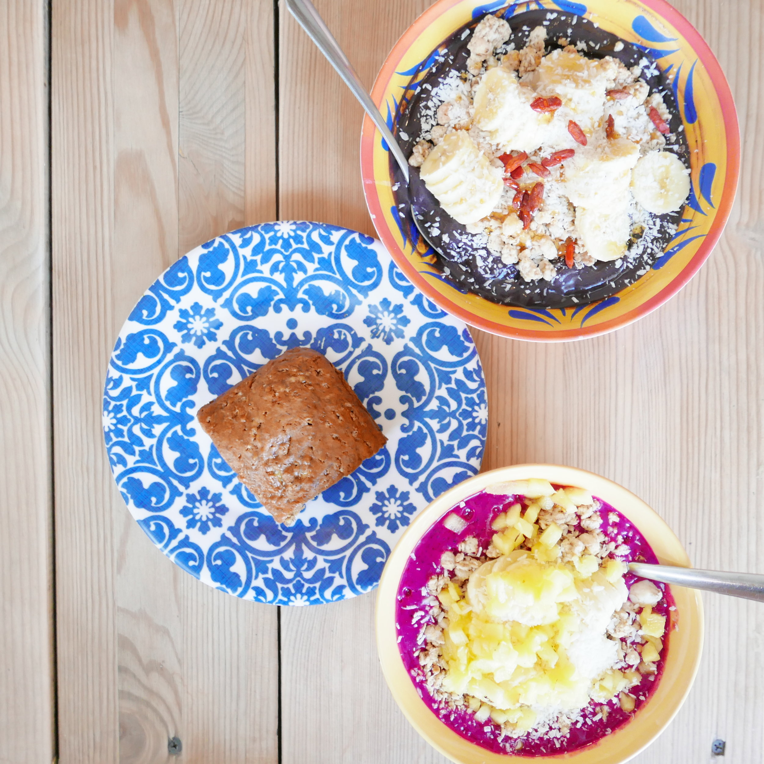 Top: Superfood Bowl - Raw acai blended with banana, spirulina and maca topped with granola, sliced banana, coconut shavings, goji berries  Bottom: Dragon Bowl - Raw dragon fruit blended with banana. Topped with granola, sliced banana, pineapple and coconut shavings.
