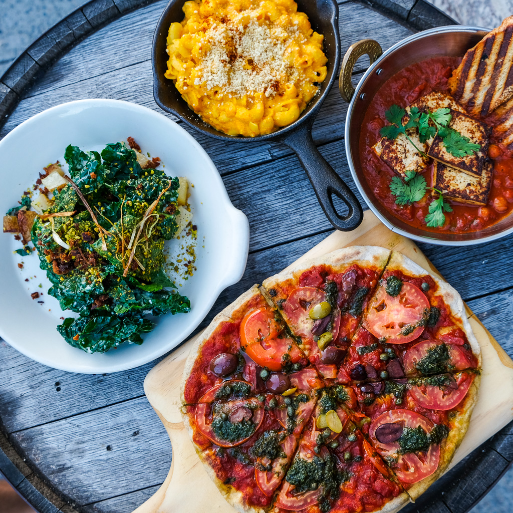 In clockwise order:  Mac and Cheese  Shakshuka - slow roasted organic tomato and chick pea stew, harissa, tofu, cilantro and grilled bread  Flatbread -Tomato, basil, olives, capers, garlic  Market greens with crispy leeks, miso crumbs, pistachio, creamy truffle dijon dressing