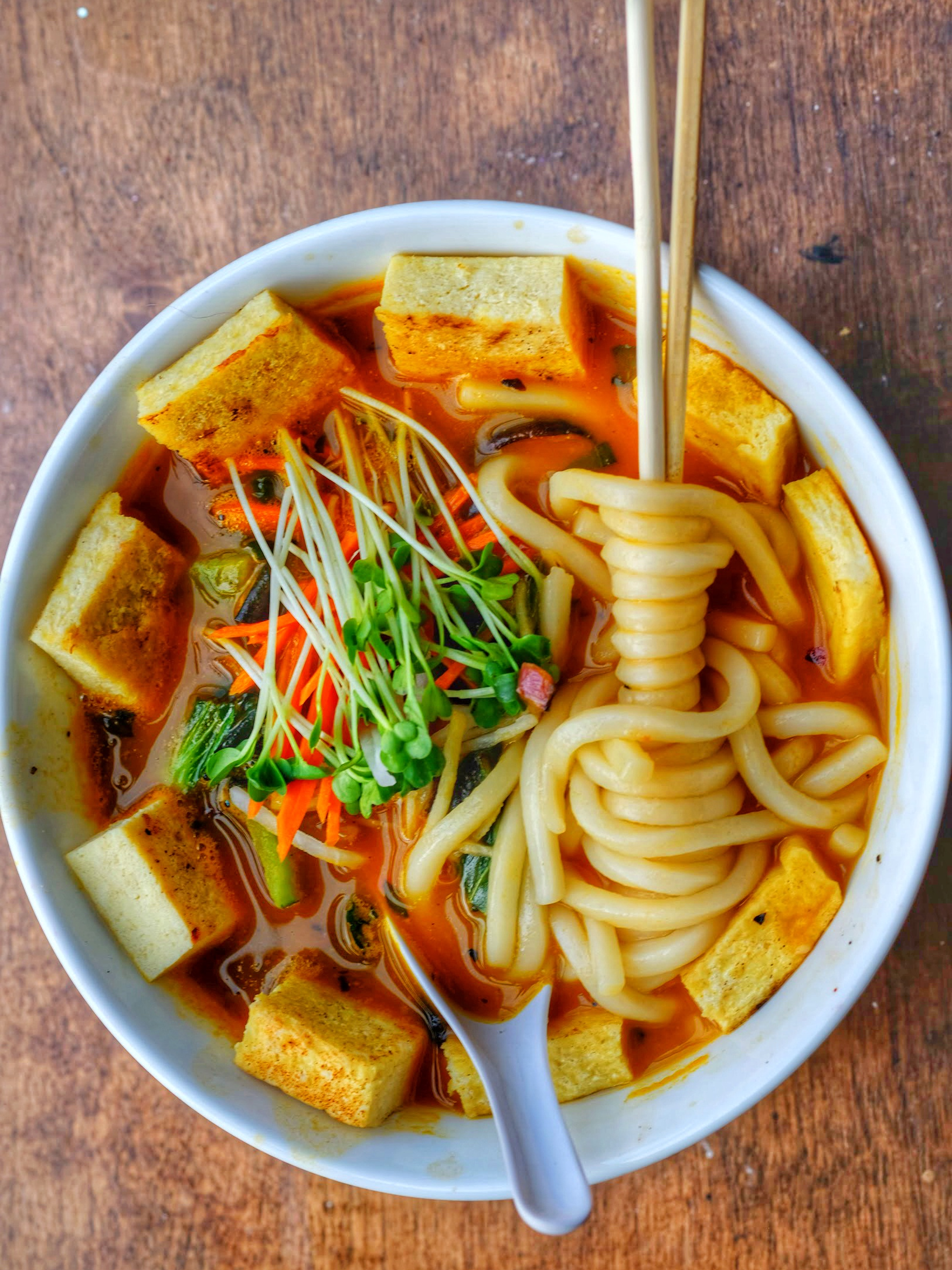 mushrooms, bok choy, fennel, shallot, jalapenos, thai basil and fresh noodles in a carrot ginger broth with daikon, pickeld carrot, sprouts
