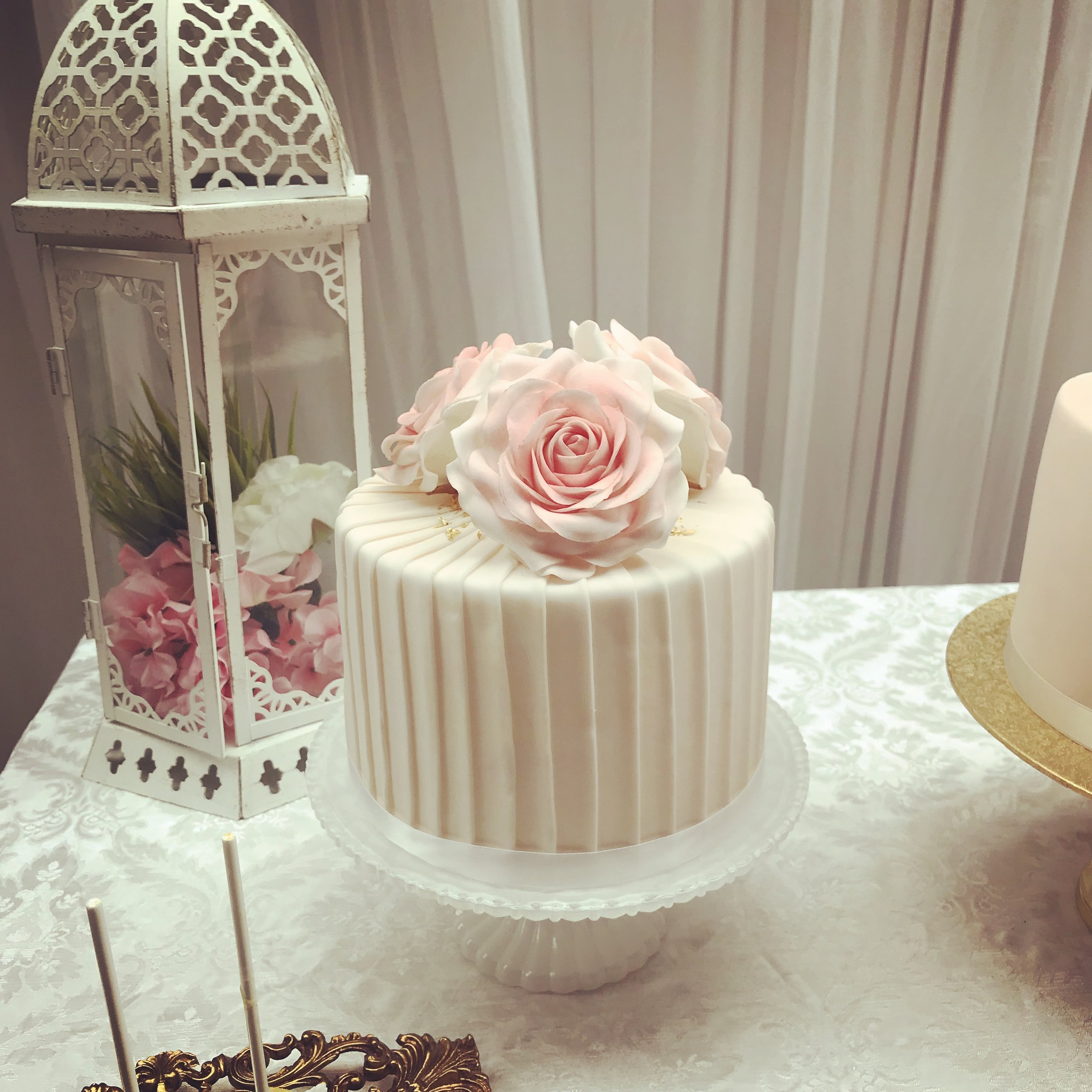 Pink sugar roses with sprinkles of gold on a pink pastel stripped wedding cake is a perfect choice for a vintage wedding too.
