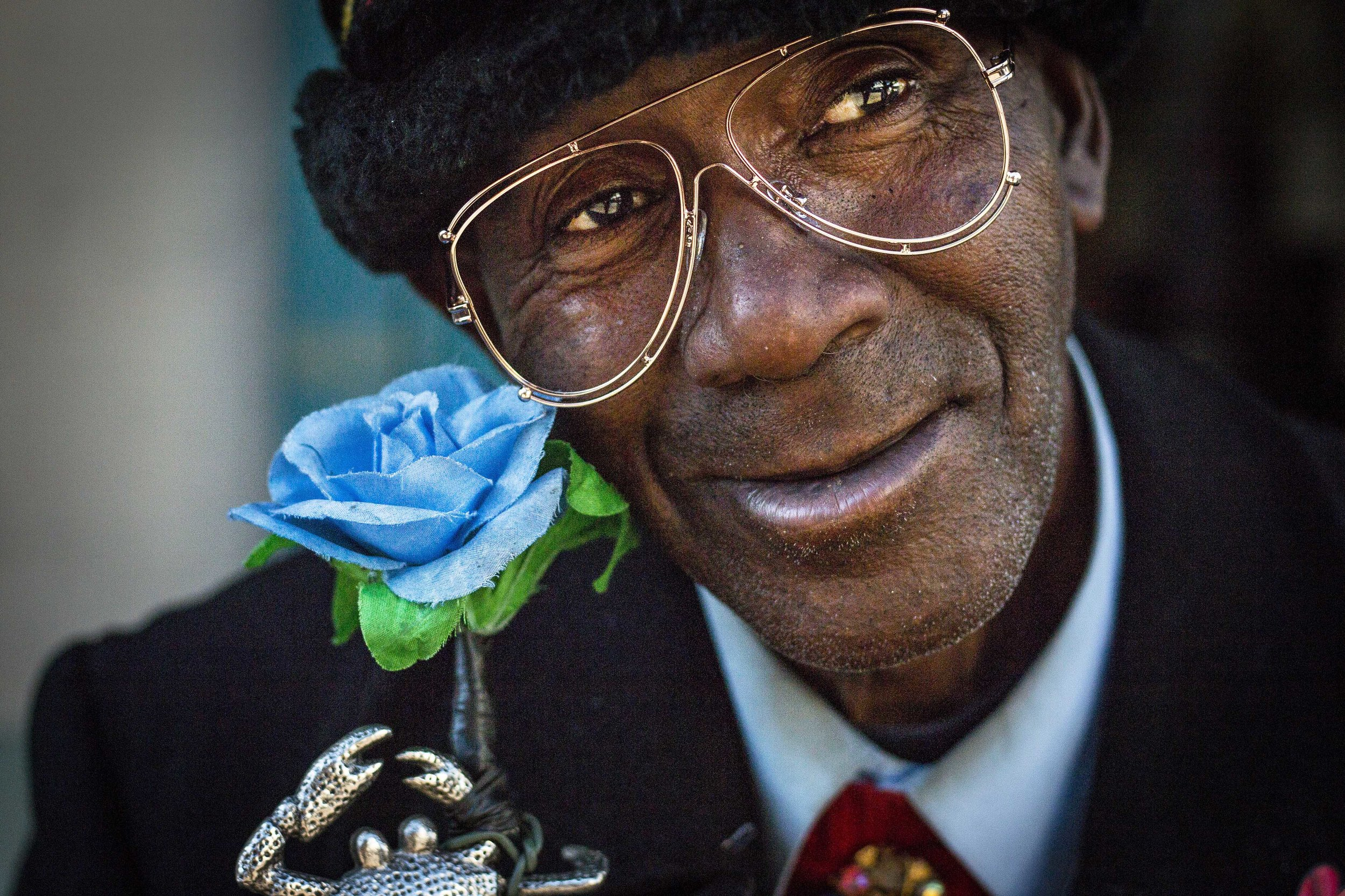 Sitting on a New Orleans stoop and resting on a cane, wrapped with a blue flower and topped with a sliver crab, Chester talks about growing up on Bourbon Street, Nov. 26, in New Orleans, Louisiana.
