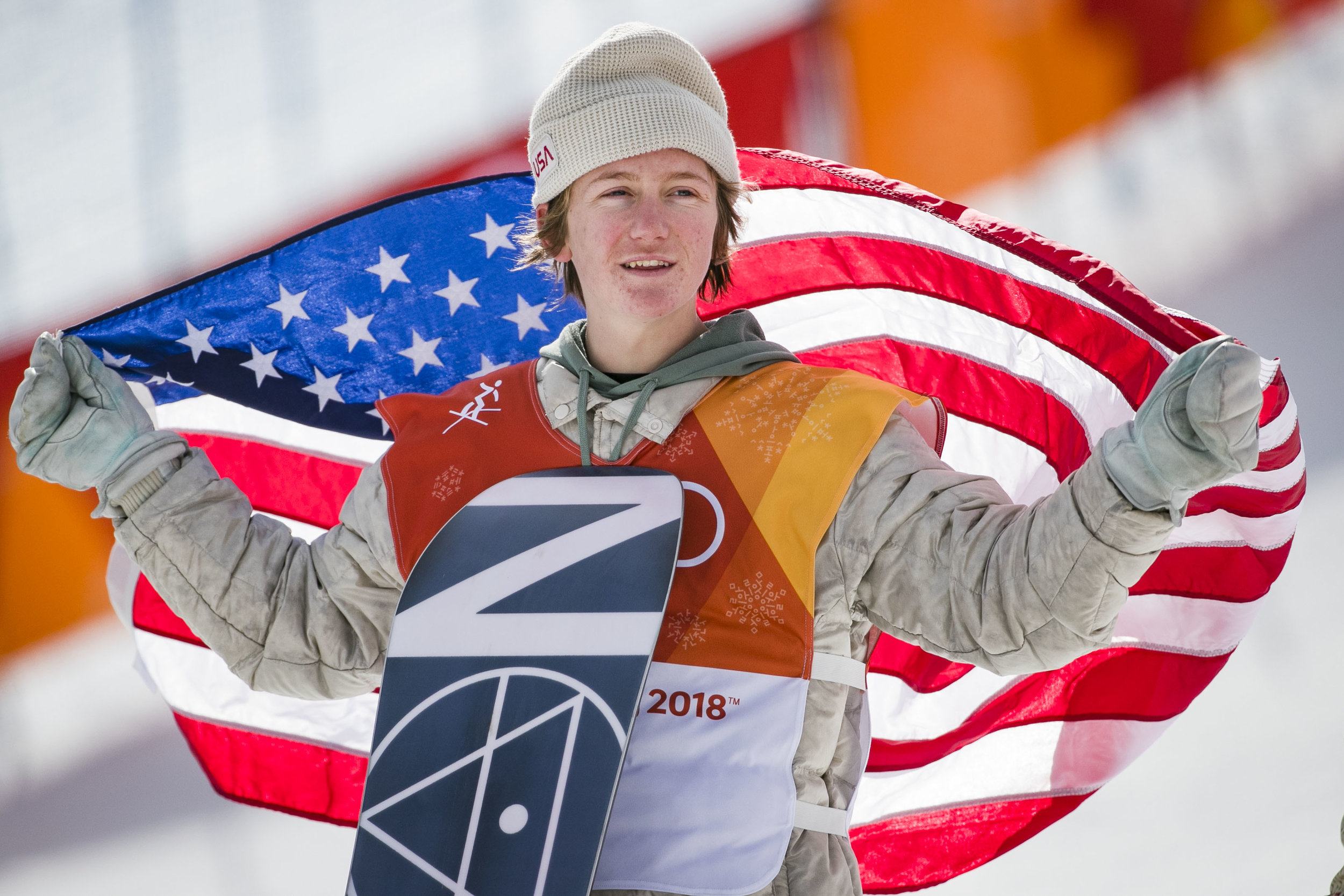 The first U.S. gold medal won by snowboard slopestyle 17-year-old Red Gerard, Feb. 11 at Phoenix Snow Park holds up an American flag during the medaling ceremony.