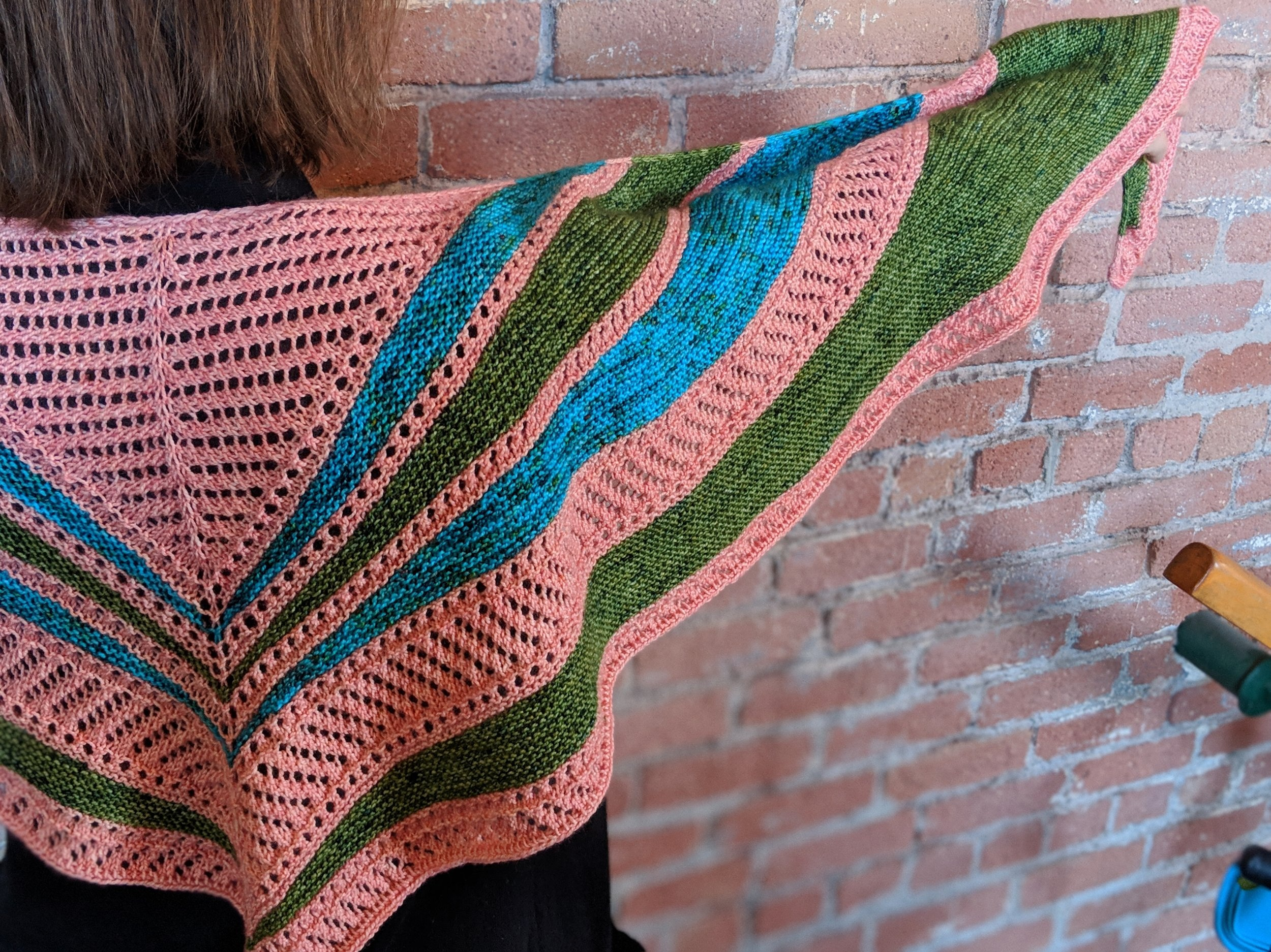 East Egg Shawl - Just before purchasing the yarn we drove by a 1920's theatre all dressed up in a similar color scheme. From the shape and colors East Egg is inspired from Art Deco architecture and named for The Great Gatsby. This is the lace version of my popular West Egg Shawl.Ellen Coy - Ellen Rose Knits#easteggshawl #ellenroseknits