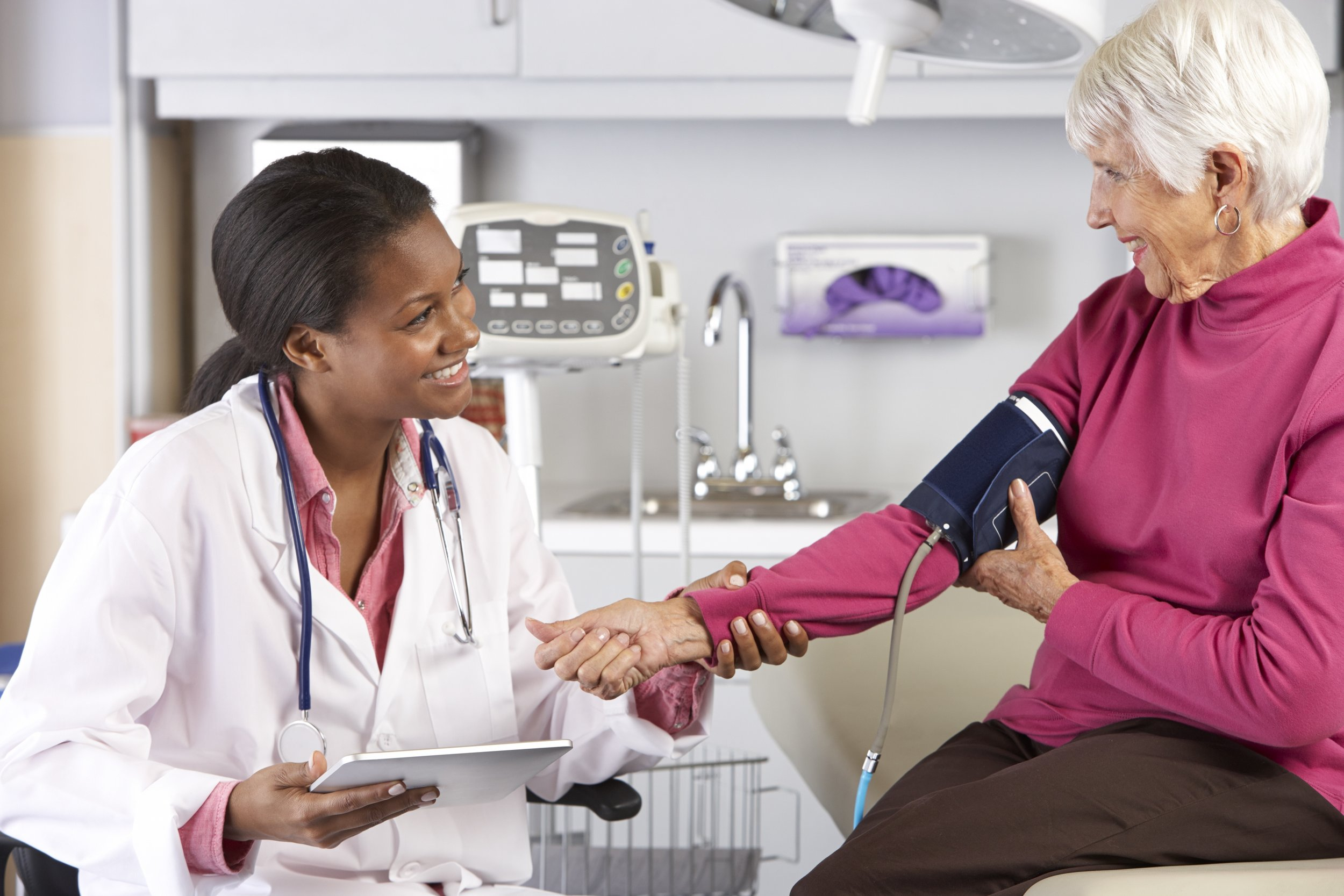 Female taking senior woman's blood pressure at a physical check up