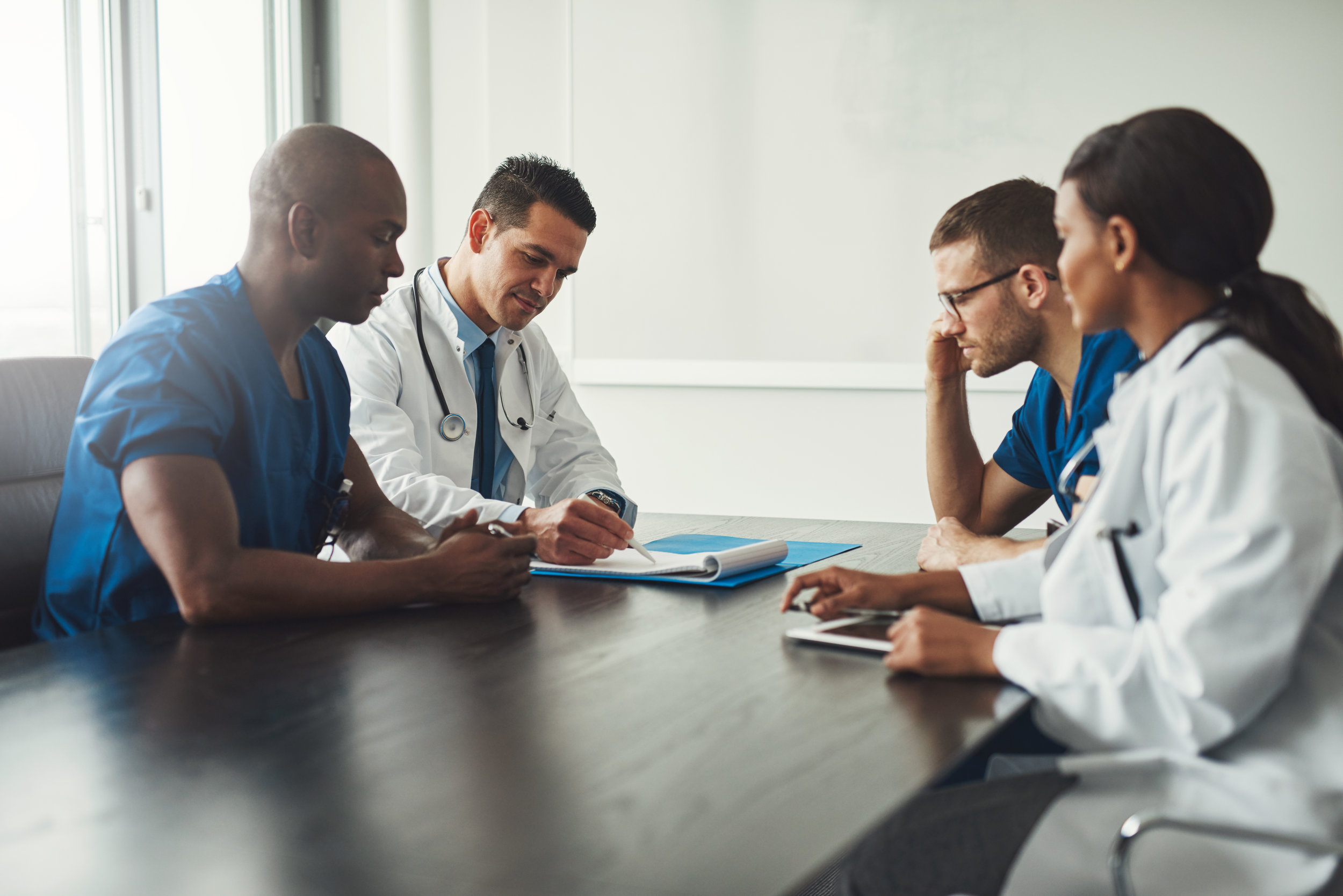 Four primary care doctors completing paperwork and evaluating patient history