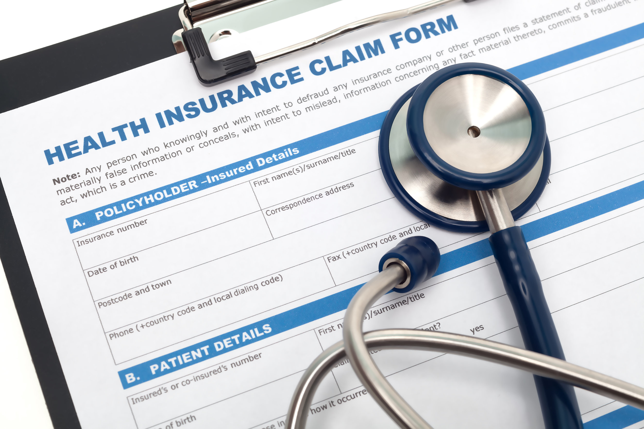 Blank copy of Insurance Claim Form for Physicians on clipboard with stethoscope overlayed