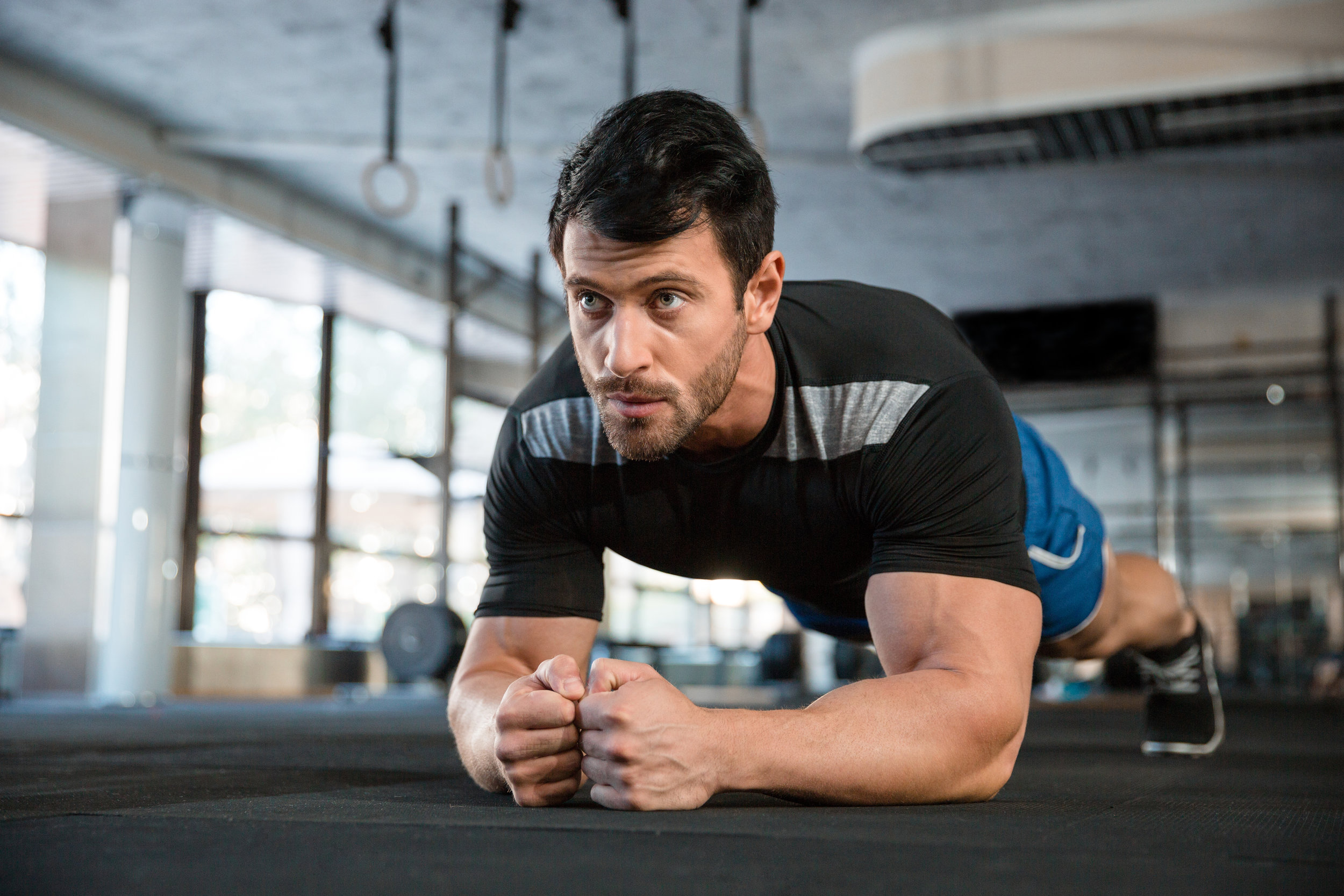 Male athlete wearing blue shorts and black t-shirt improving overall body composition through physical exercises