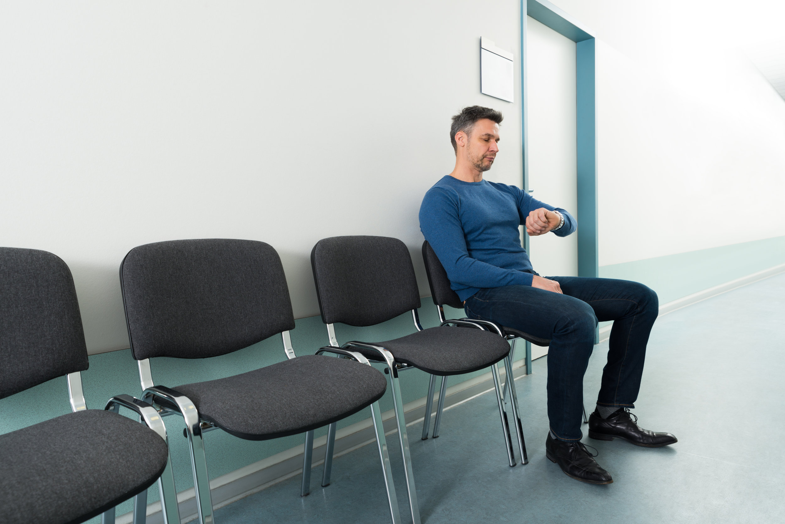 Impatient man in the waiting room waiting for doctor's appointment