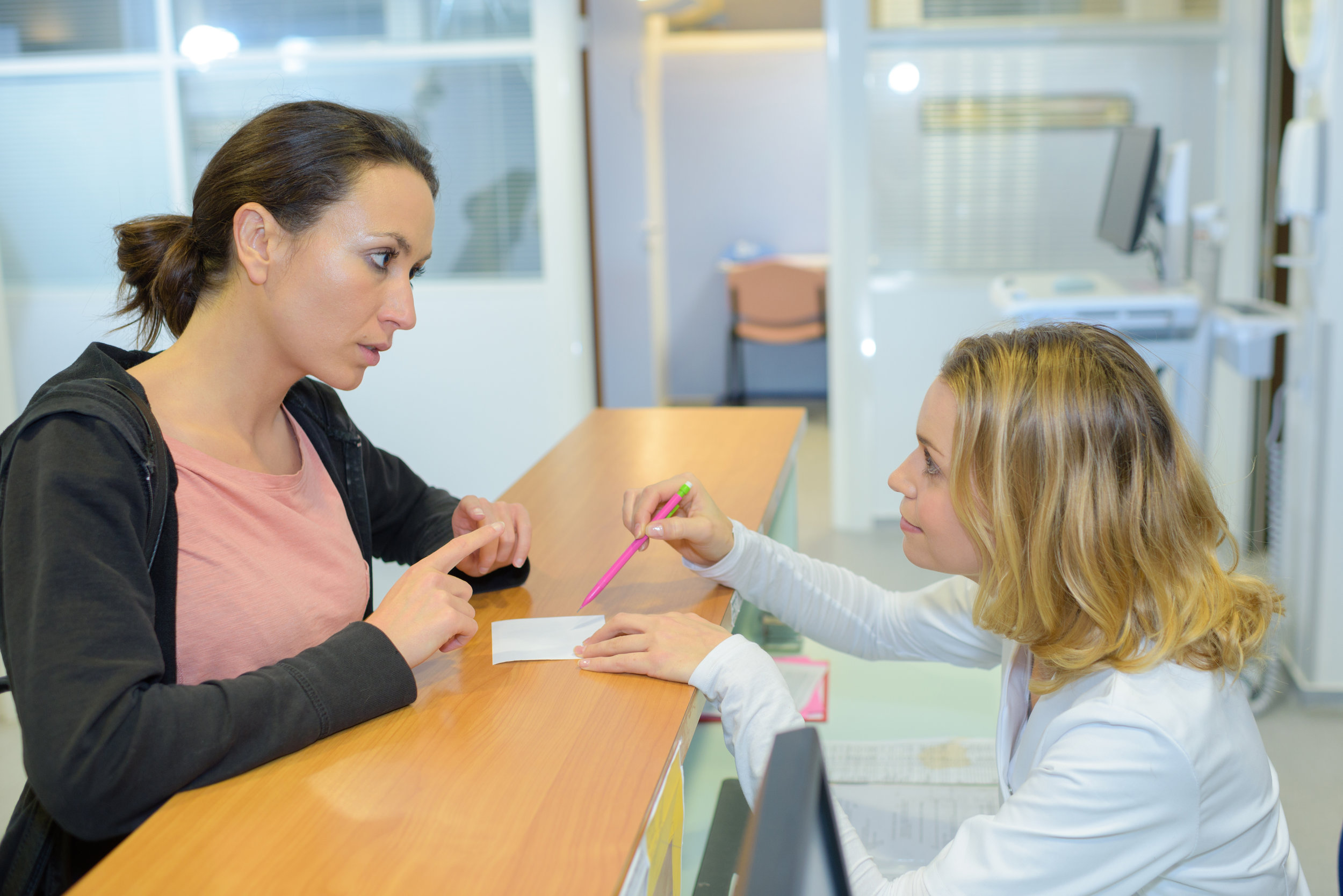 A frustrated patient signing additional forms in the doctor's waiting room
