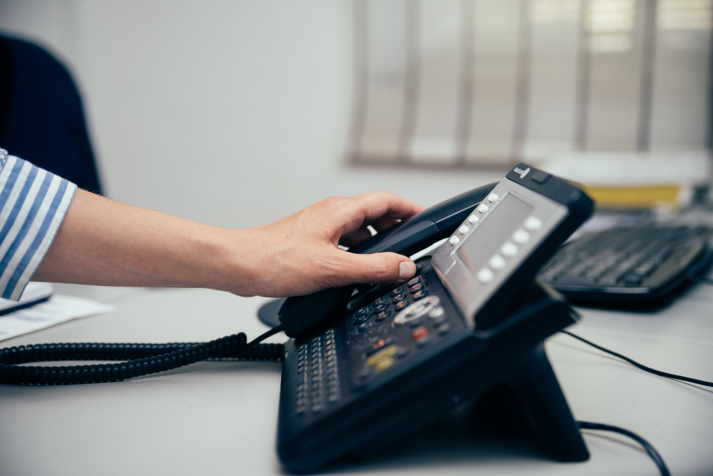 A receptionist picking up the telephone to answer patients' calls