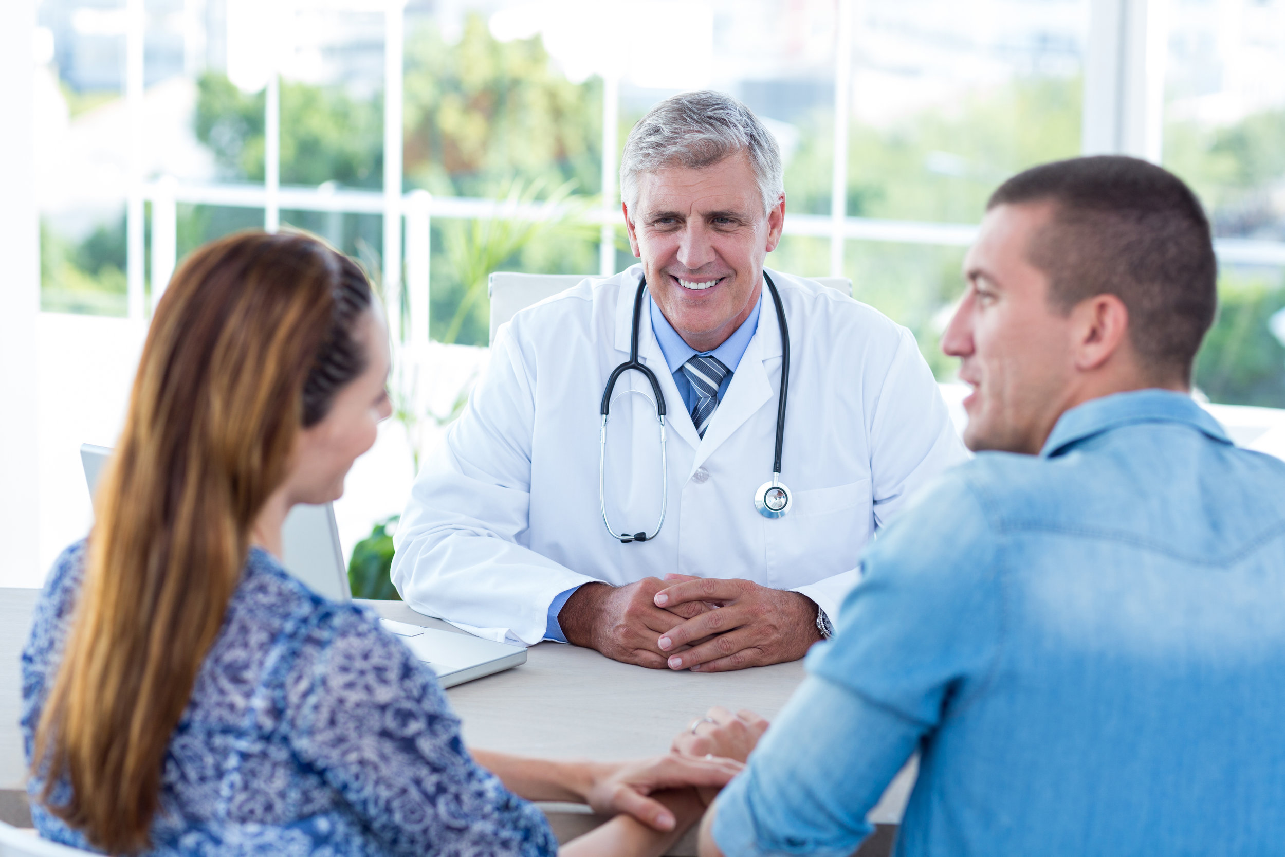 A kind doctor meeting with a young couple about their health during a doctor's appointment