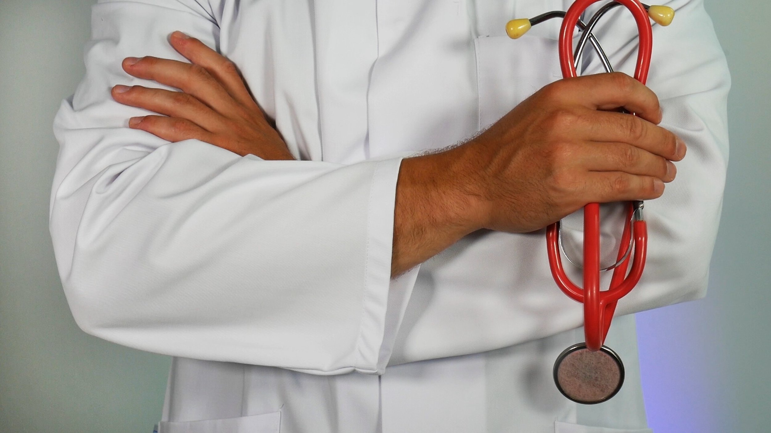 Direct primary care doctor dressed in a white coat with crossed arms and a red stethoscope overlayed