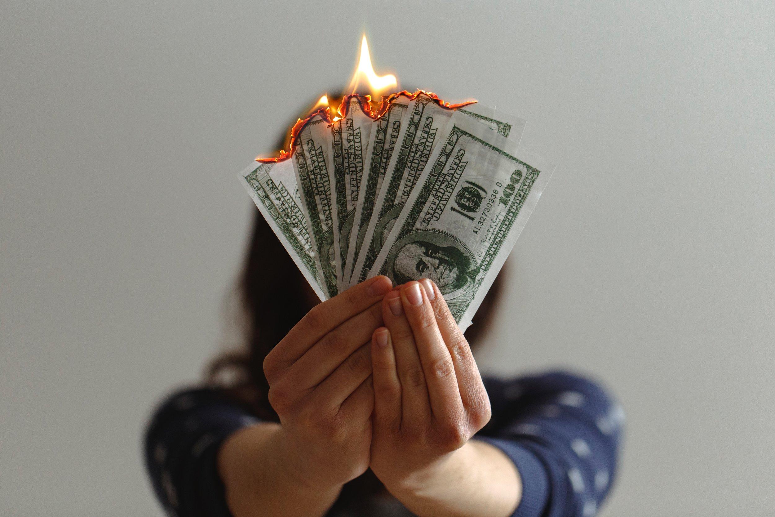 Female in blue shirt holding a fan of dollar bills on fire