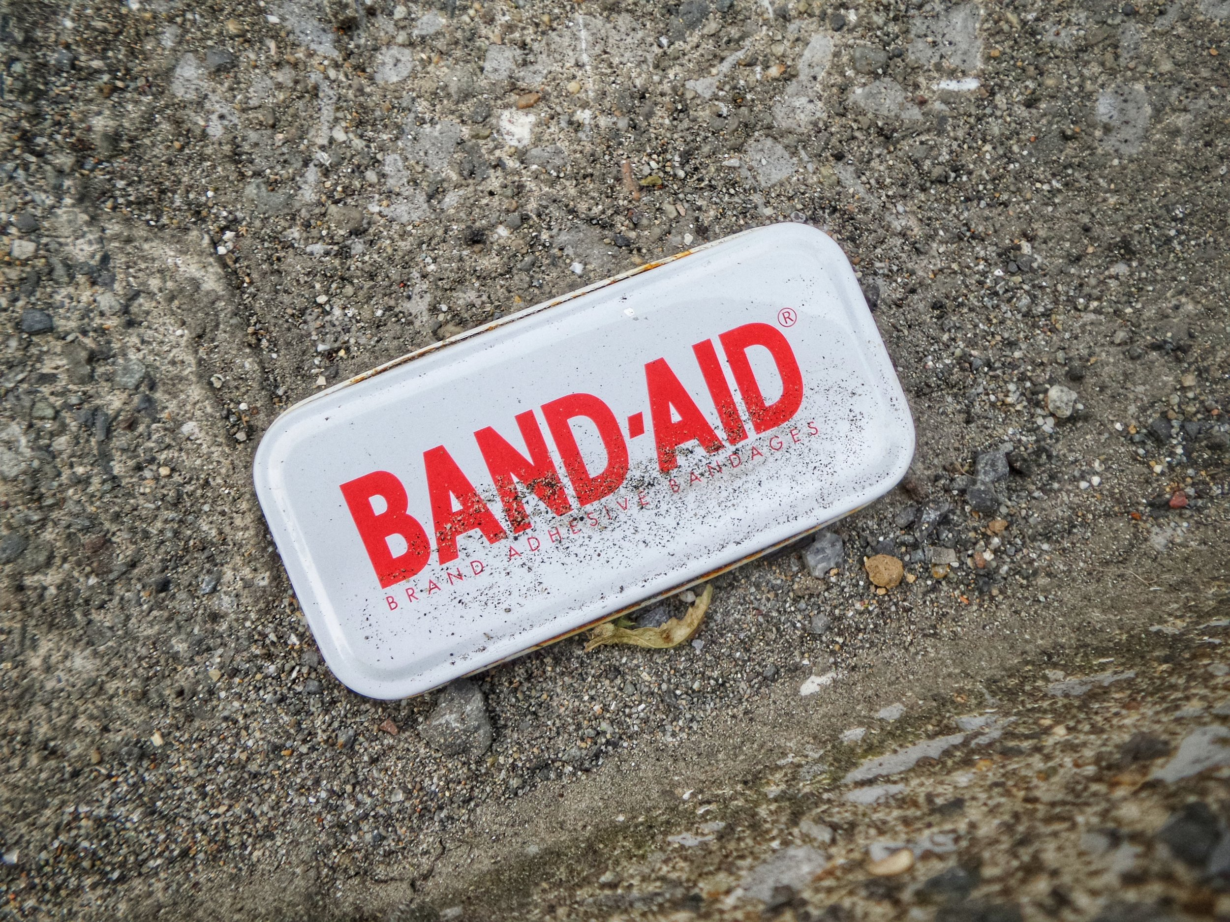 White tin Band-Aid container laying on curb, covered in sand