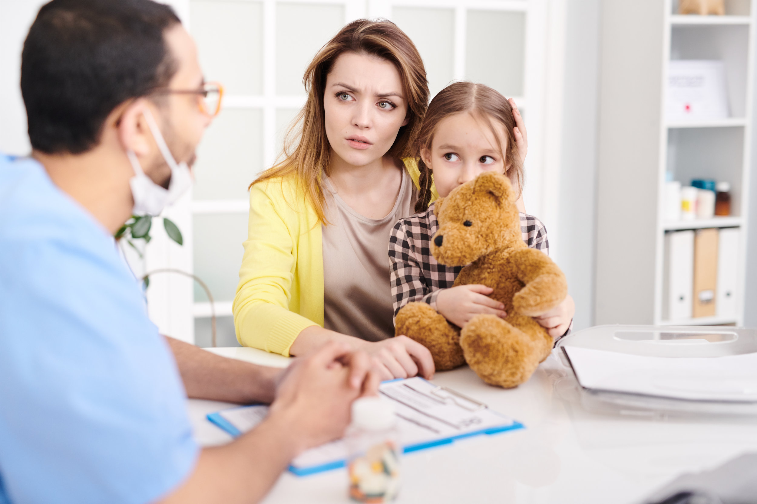 Concerned mother and daughter in primary care office consulting with a male primary care physician