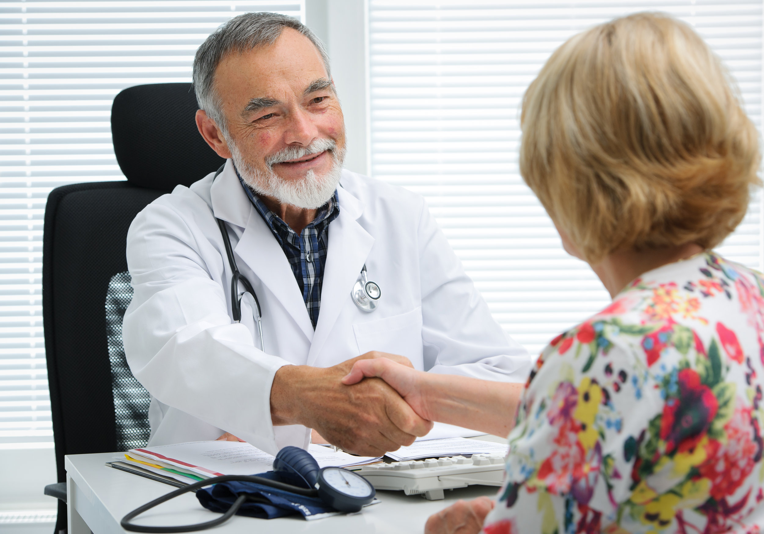 Friendly male family doctor greeting female patient at an annual appointment with a handshake