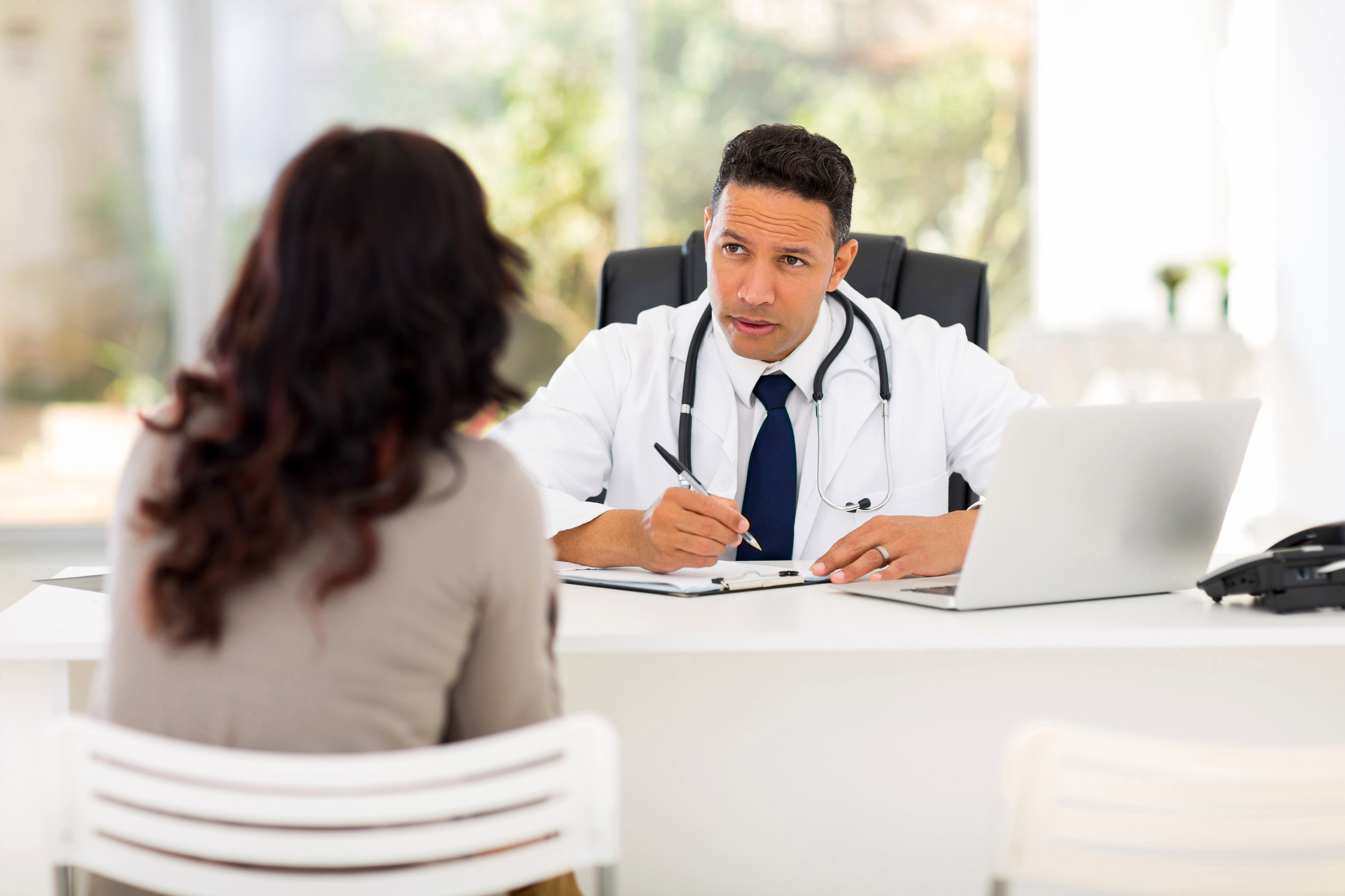 Professional medical doctor consulting with female patient in office, encouraging physician patient interaction