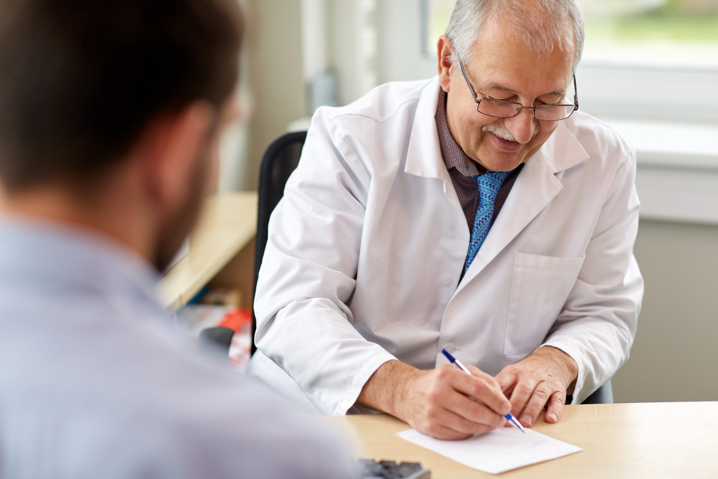 Older male doctor writing a prescription for male patient at a clinic