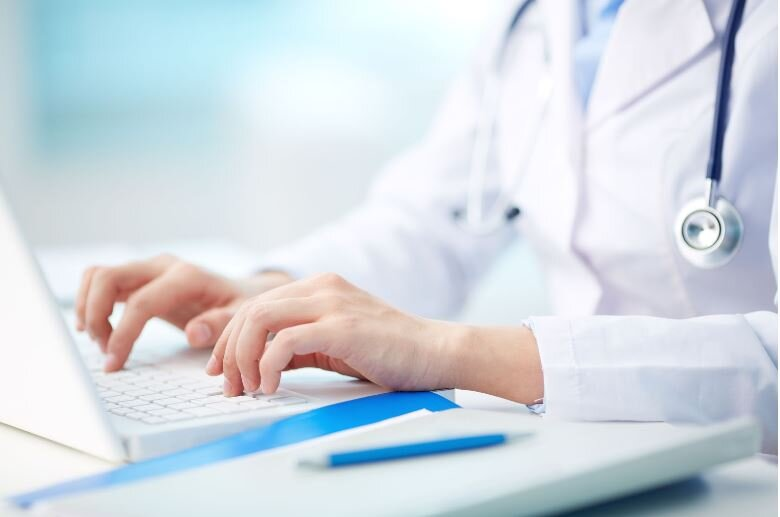Medical doctor in white coat typing information into a computer