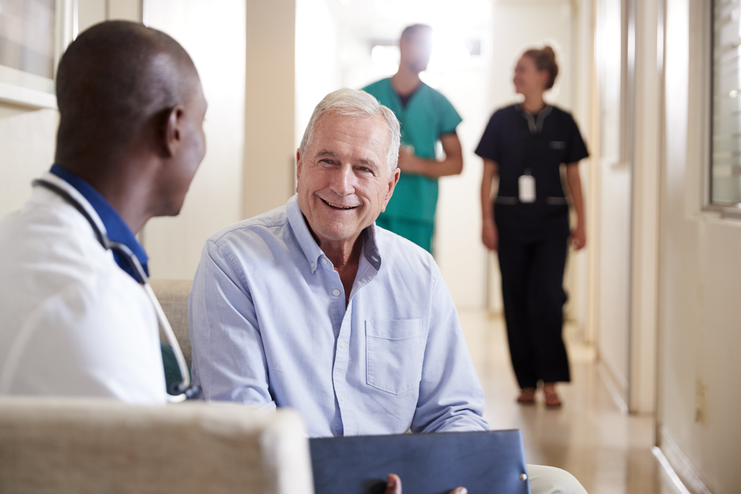 Smiling patient meeting with his doctor to talk about test results in hospital hallway