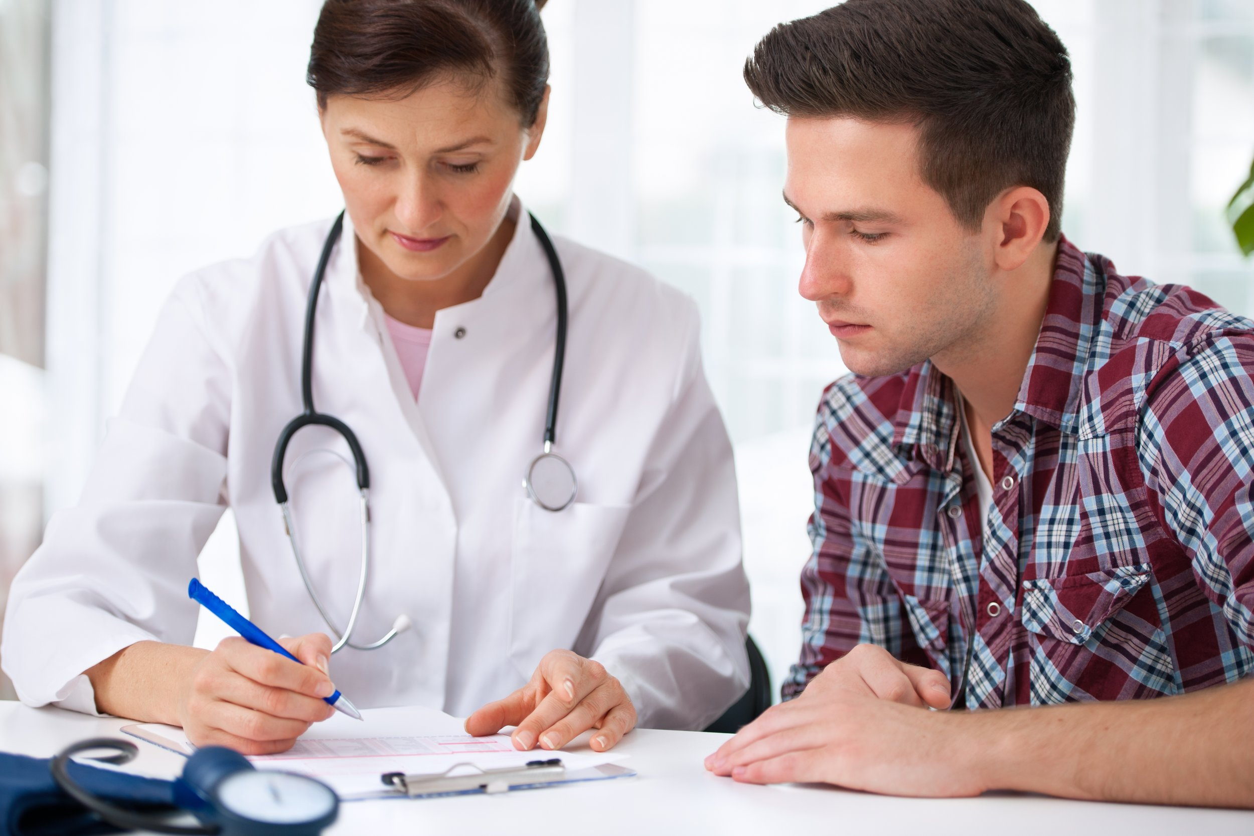 Medical doctor going over insurance and medical bills with male patient