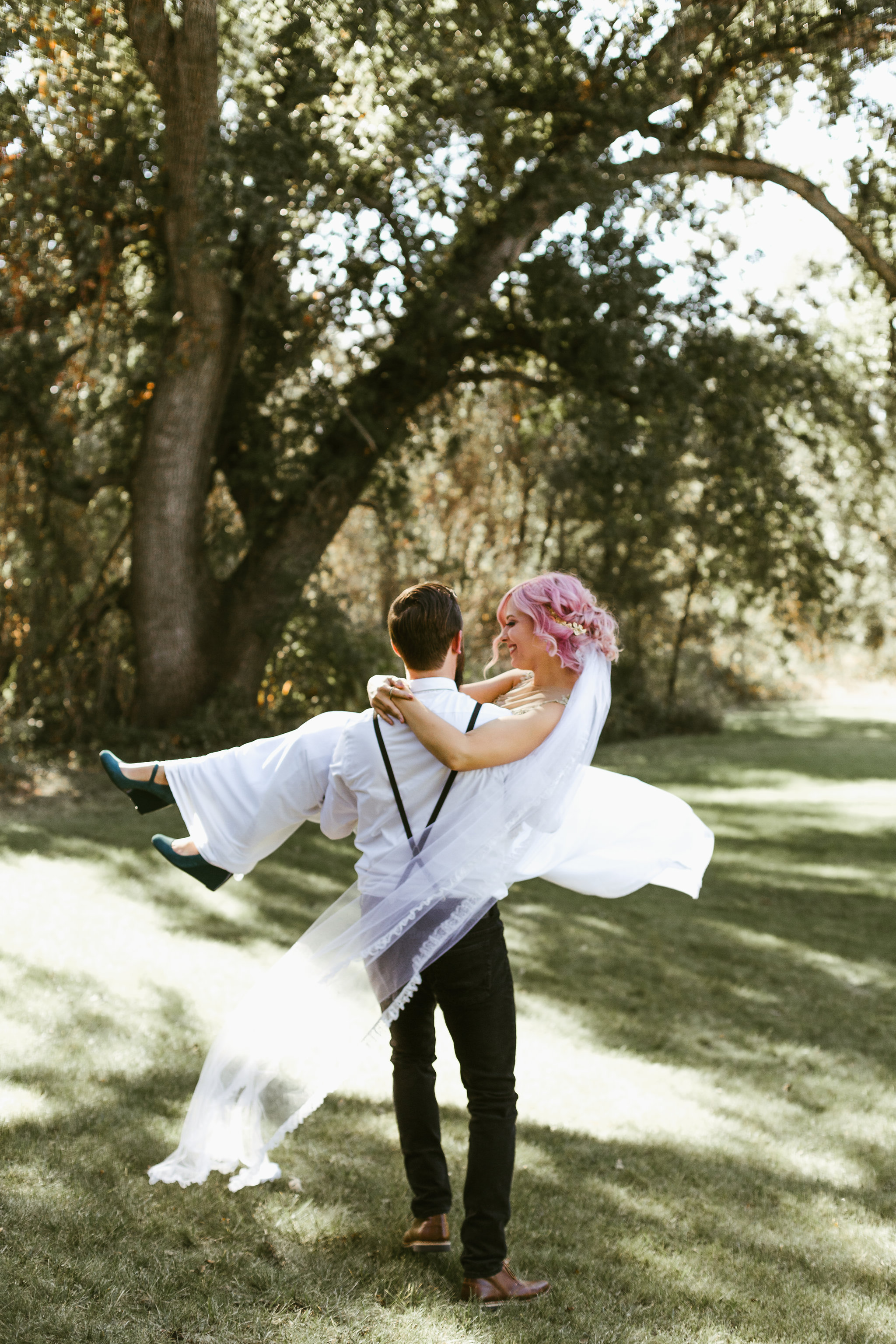 Groom twirling Bride with pink hair and gold wedding dress