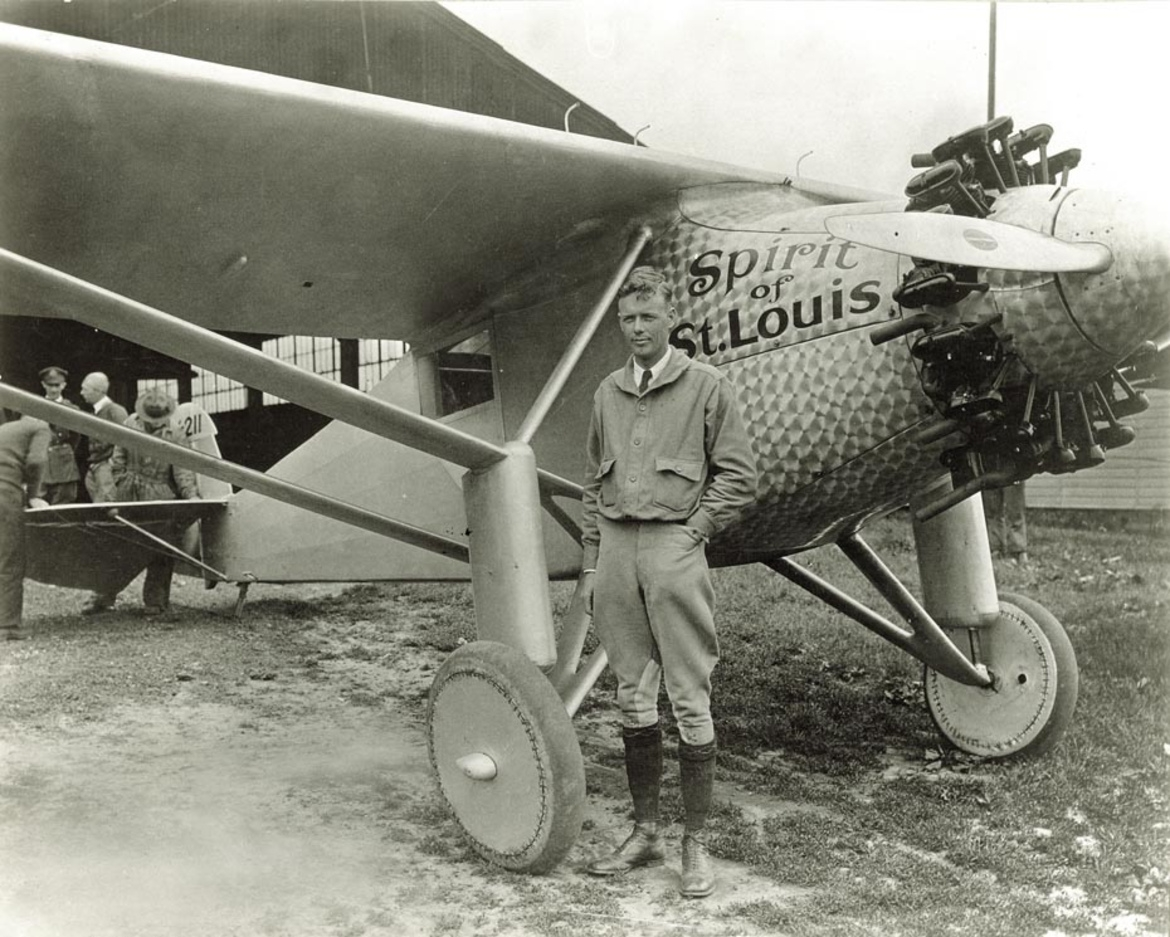 Charles Lindbergh standing beside the Spirit of St. Louis monoplane