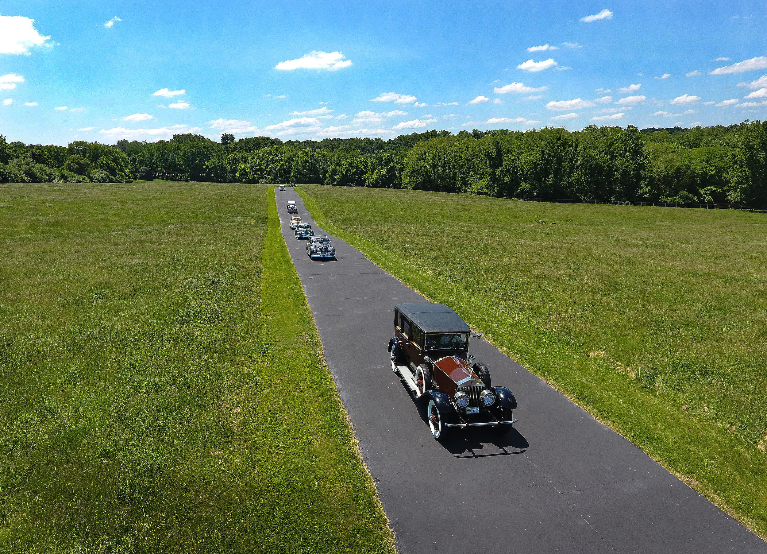 Cars entering the grounds of Hunter Farms led by Randall Andrae's 1925 Rolls-Royce