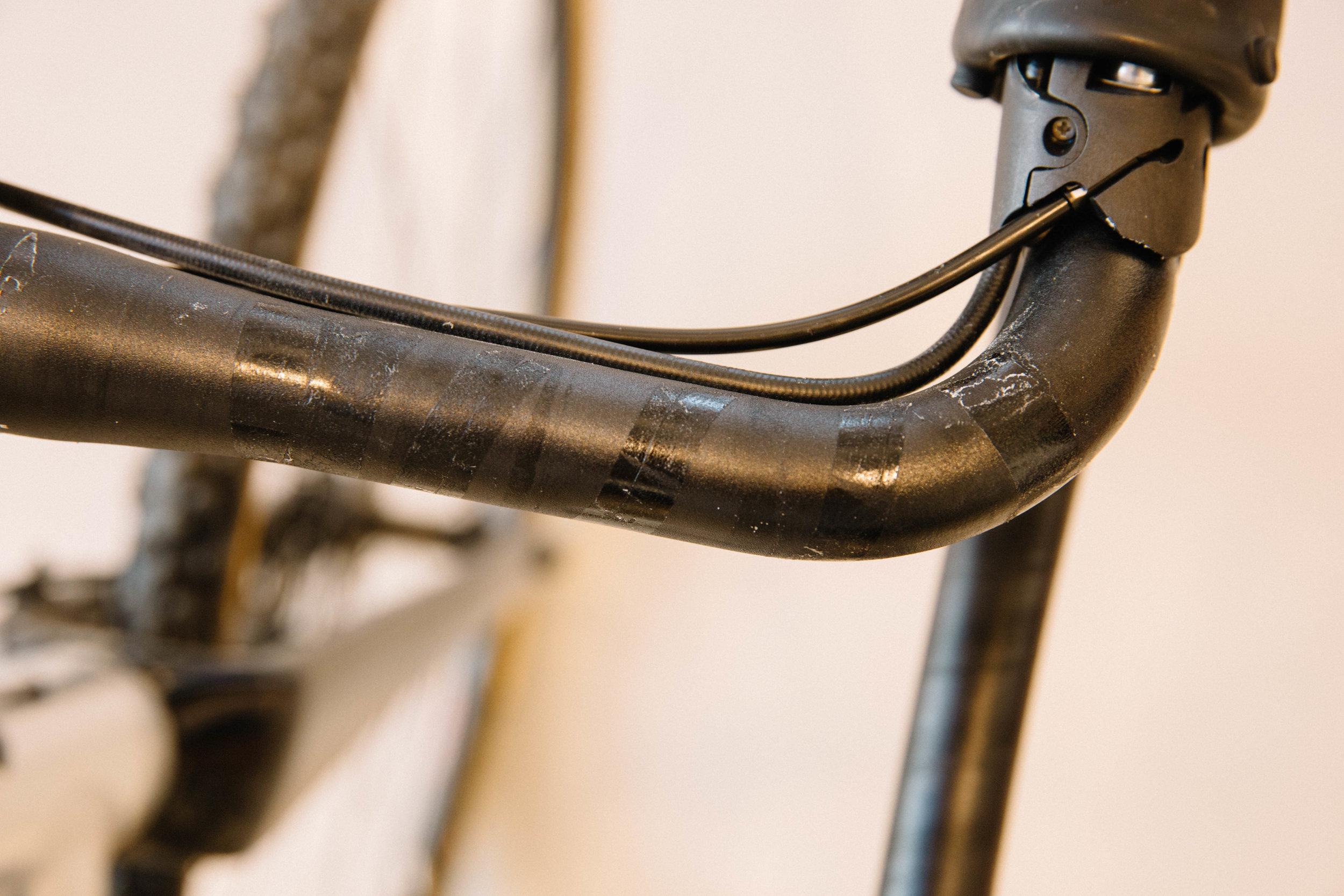 Die abgezogenen Klebestreifen bleiben fast immer noch am Lenker haften, dazwischen kleben noch Überreste des alten Lenkerbandes.