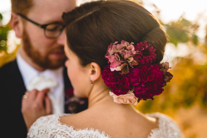 brud med mørk rosa blomst i håret