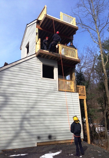 Junior Firefighter Peyton Galloway rappels from the 25' level of Wintergreen Fire & Rescue's new training tower while instructor Nick Brown offers pointers and firefighter/medic Eric nhold belays.