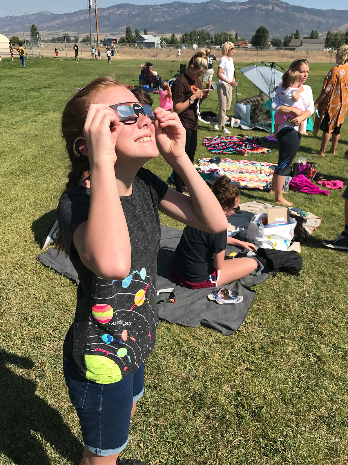 A girl watches the solar eclipse through eclipse glasses.