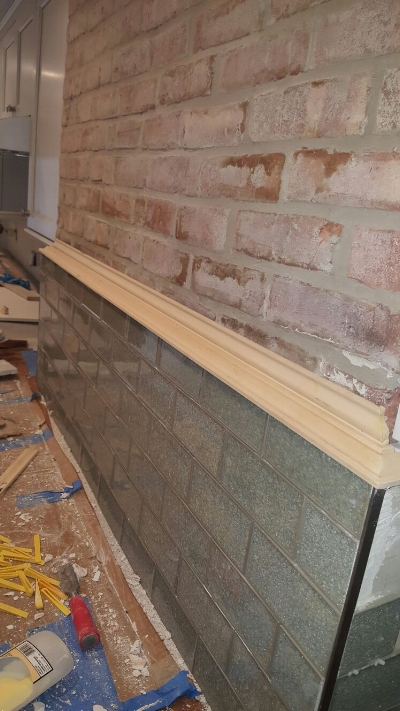 Custom moulding integrating existing brick work with new backsplash in a kitchen