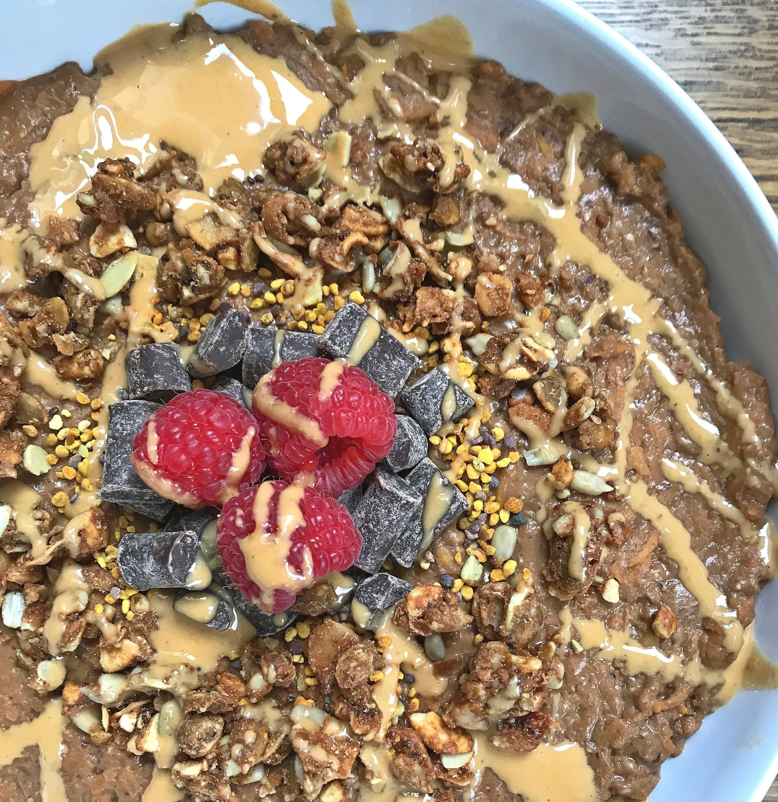 Topped with grain-free granola, bee pollen, vegan chocolate chunks, raspberries and melted cashew butter.