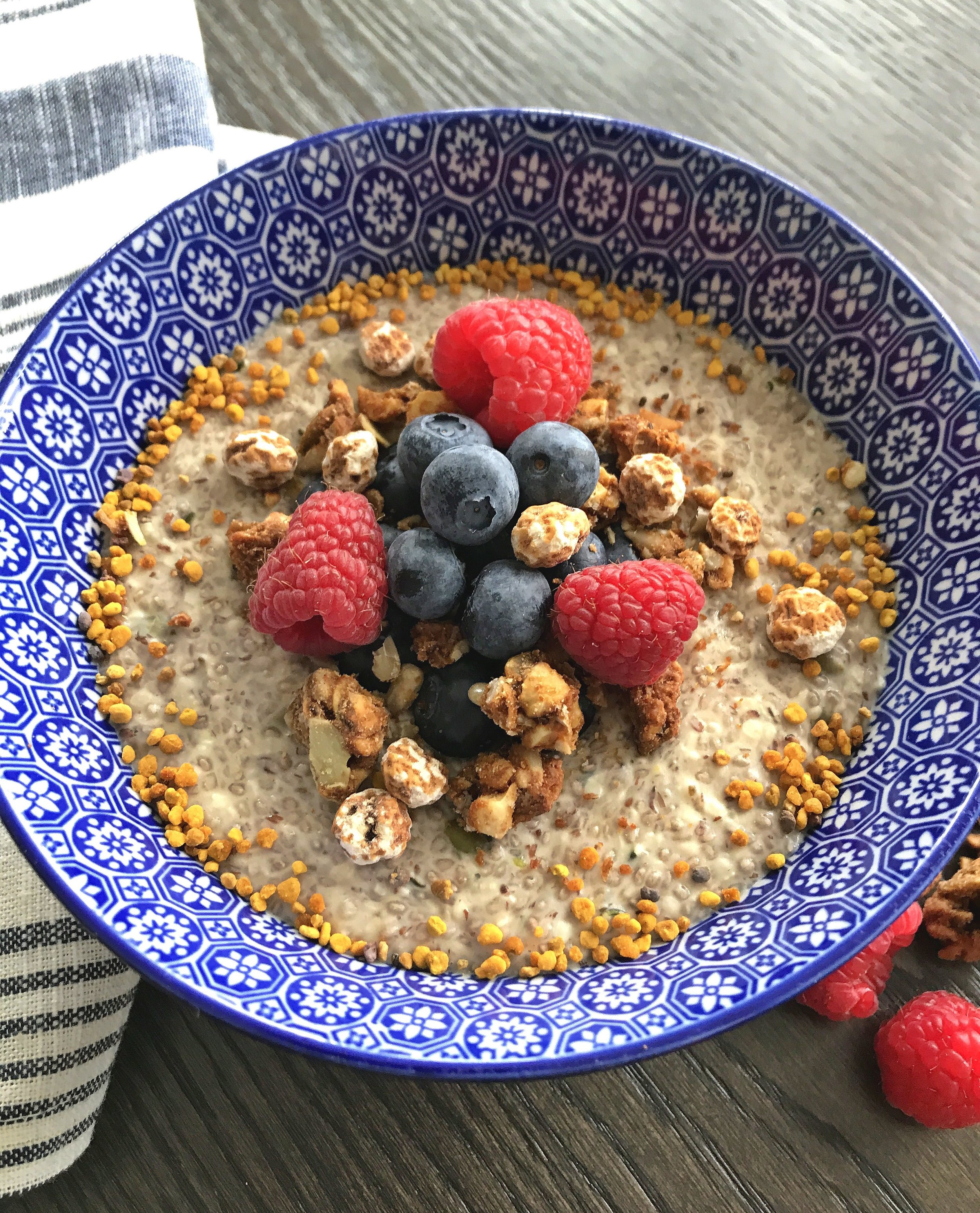 Super Seedy Protein Porridge topped with fresh berries, granola, peeled tiger nuts, and bee pollen.