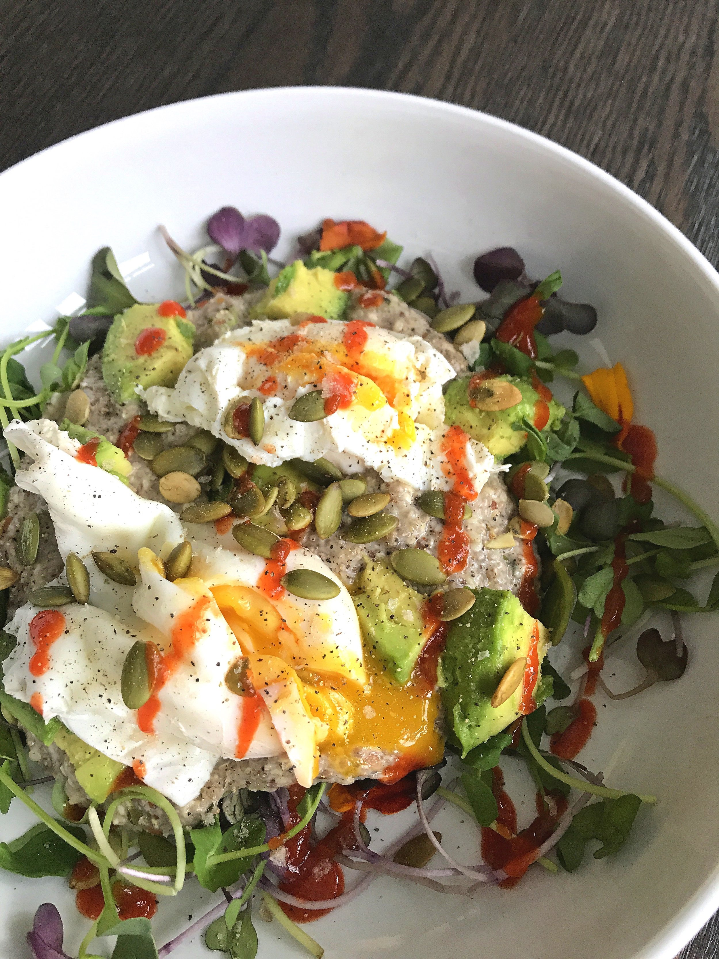 Super Seedy Protein Porridge served with microgreens, diced avocado, pasture-raised poached egg, toasted pumpkin seeds, and sriracha.