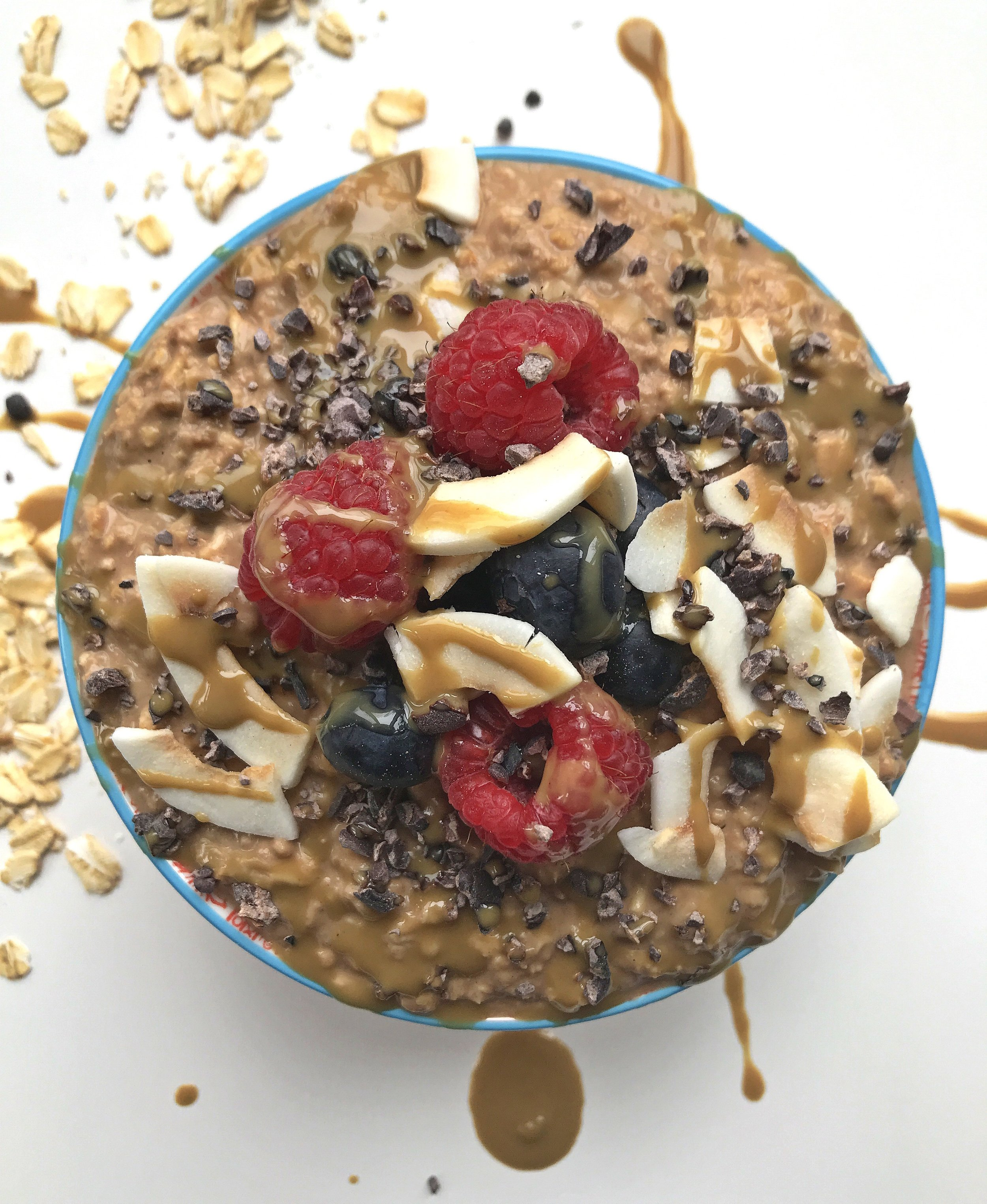 """""""REESE'S"""" PEANUT BUTTER PROBIOTIC PROATS MADE WITH KEFIR IN PLACE OF ALMOND MILK. TOPPED WITH BERRIES, CACAO NIBS, COCONUT CHIPS, AND SUNBUTTER MELTED WITH A TOUCH OF COCONUT OIL."""