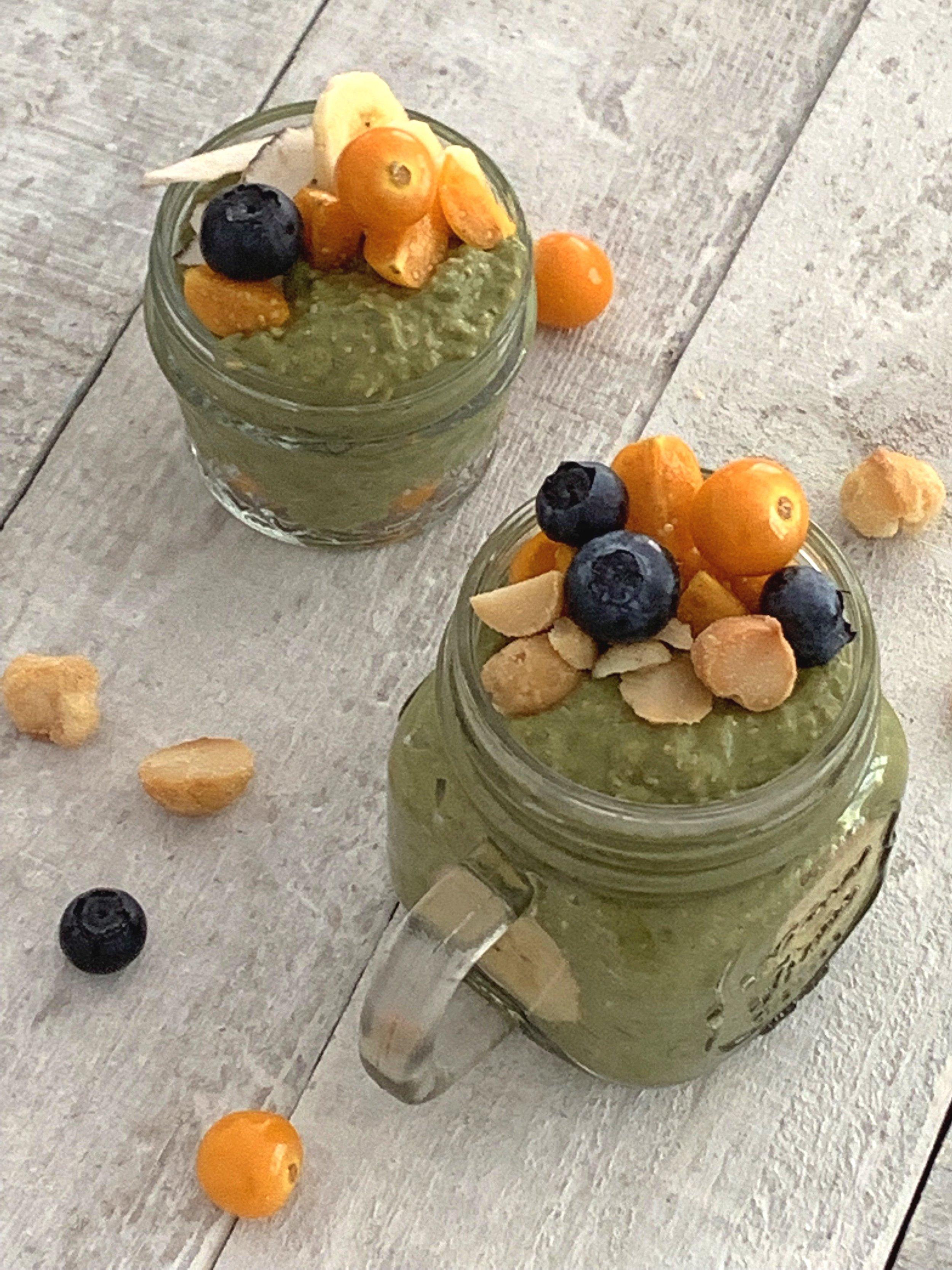 Matcha Coconut Chia Pudding made with Nuzest Clean Lean protein and topped with blueberries, golden berries, and macadamia nuts.