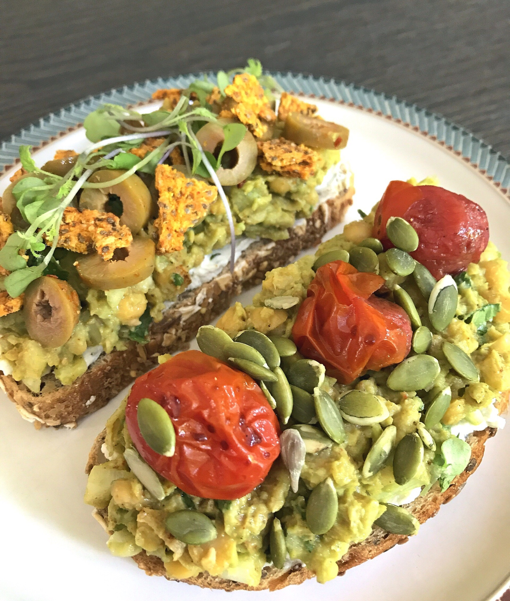 Smashed Chickpea & Avocado Salad served on toasted sourdough with vegan almond milk cream cheese, and (L) diced spicy olives, microgreens, and vegan BBQ crackers, and (R) roasted grape tomatoes and pumpkin seeds.