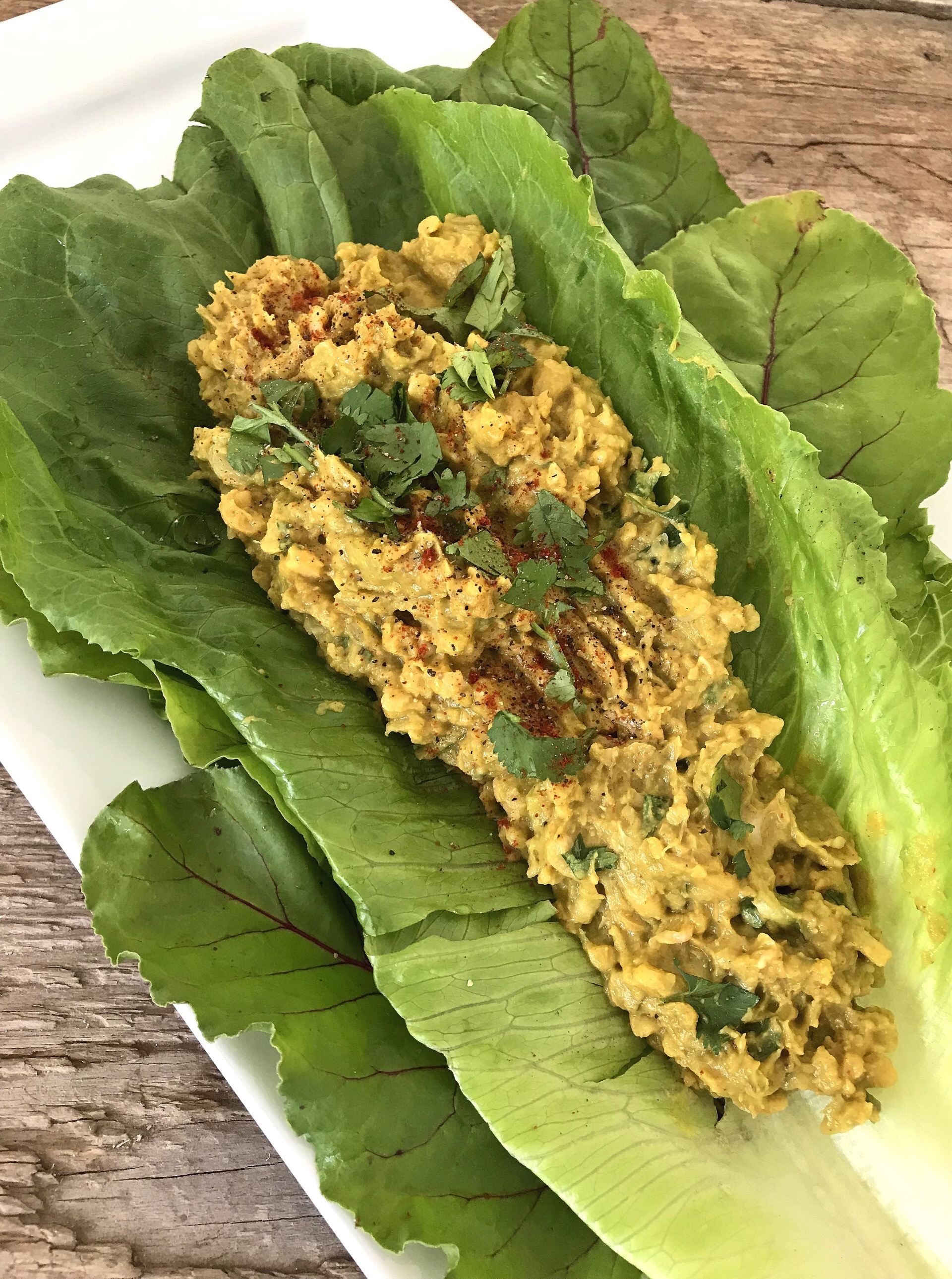 Smashed Chickpea & Avocado Salad with cilantro, served in a lettuce wrap.