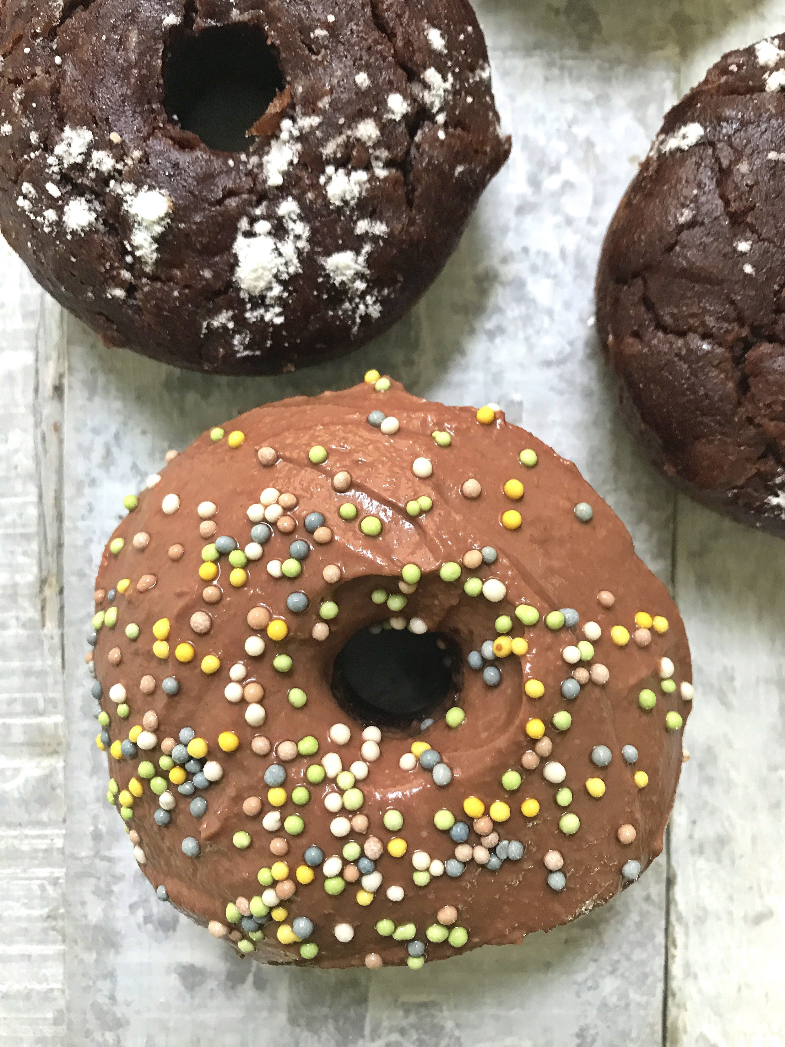 """Double Chocolate Banana Tahini Donuts topped with sugar-free confectioners', chocolate yogurt """"icing"""" (with cacao powder), and naturally-coloured sprinkles."""