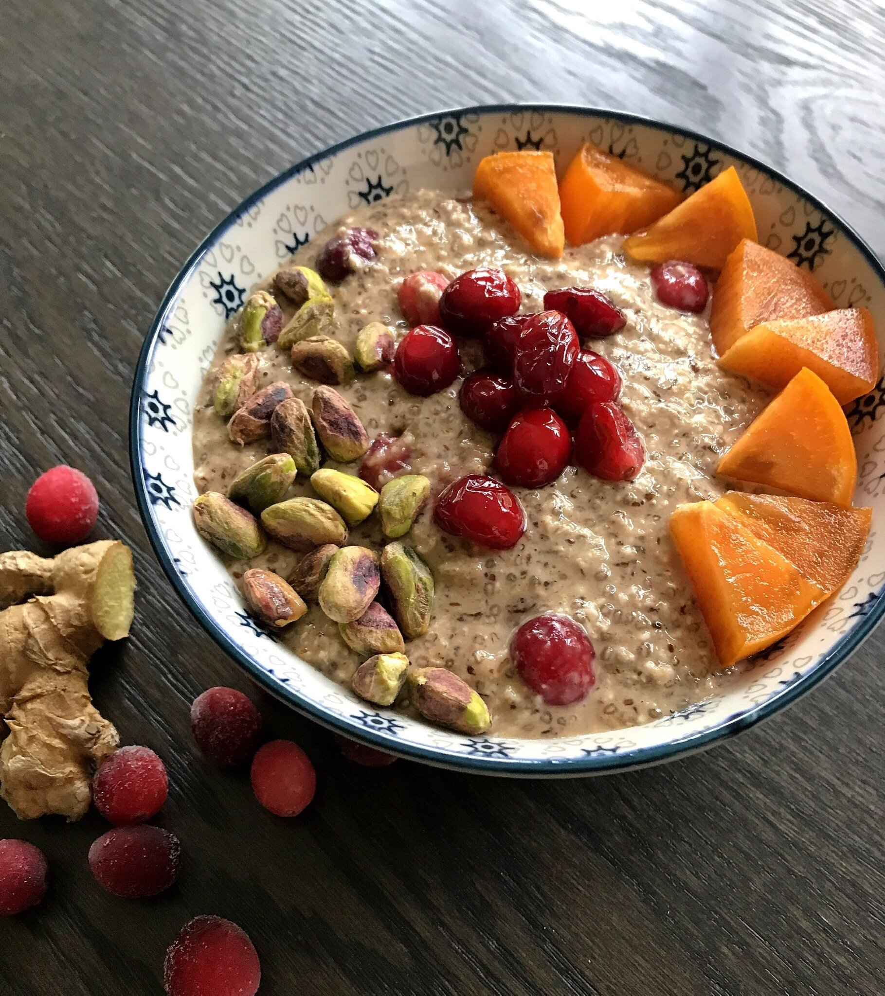 Cranberry Ginger Overnight Protein Oats topped with pistachios, diced persimmon, and warm cranberry compote (frozen berries heated with with  Beekeeper's Naturals  raw honey or pure maple syrup).