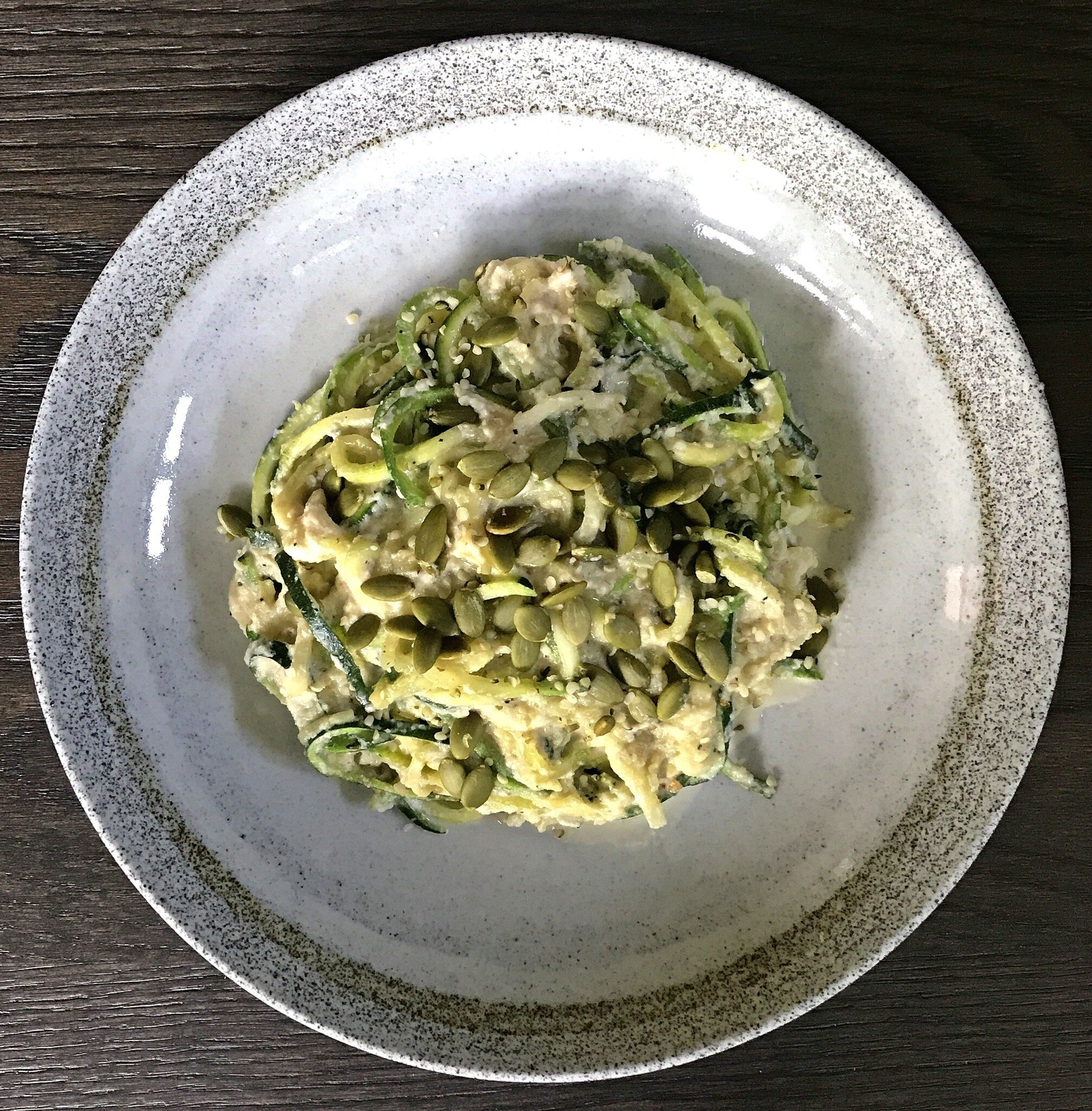 """Dairy-free """"Alfredo"""" Sauce served with spiralized zucchini and topped with hemp hearts and pumpkin seeds."""