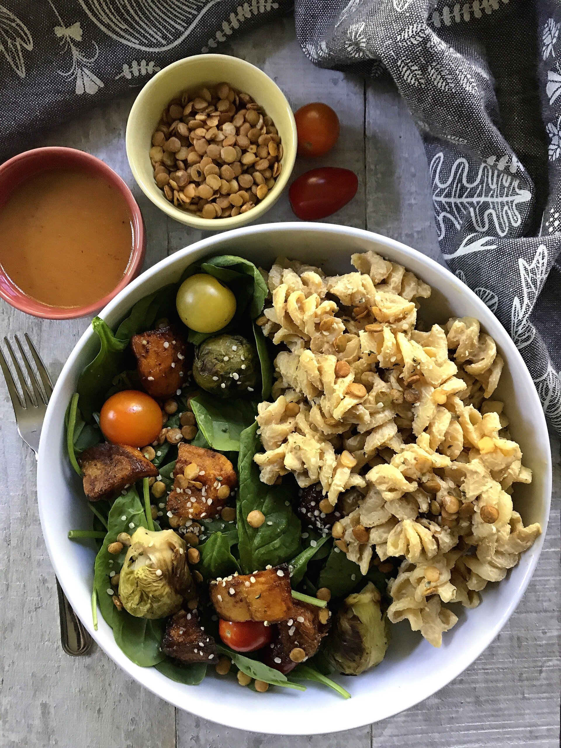 """Dairy-free """"Alfredo"""" on rotini pasta. Served with a mixed salad of spinach, grape tomatoes, roasted brussels sprouts, air-fried spicy butternut squash, and topped with crunchy BBQ lentils and hemp hearts."""