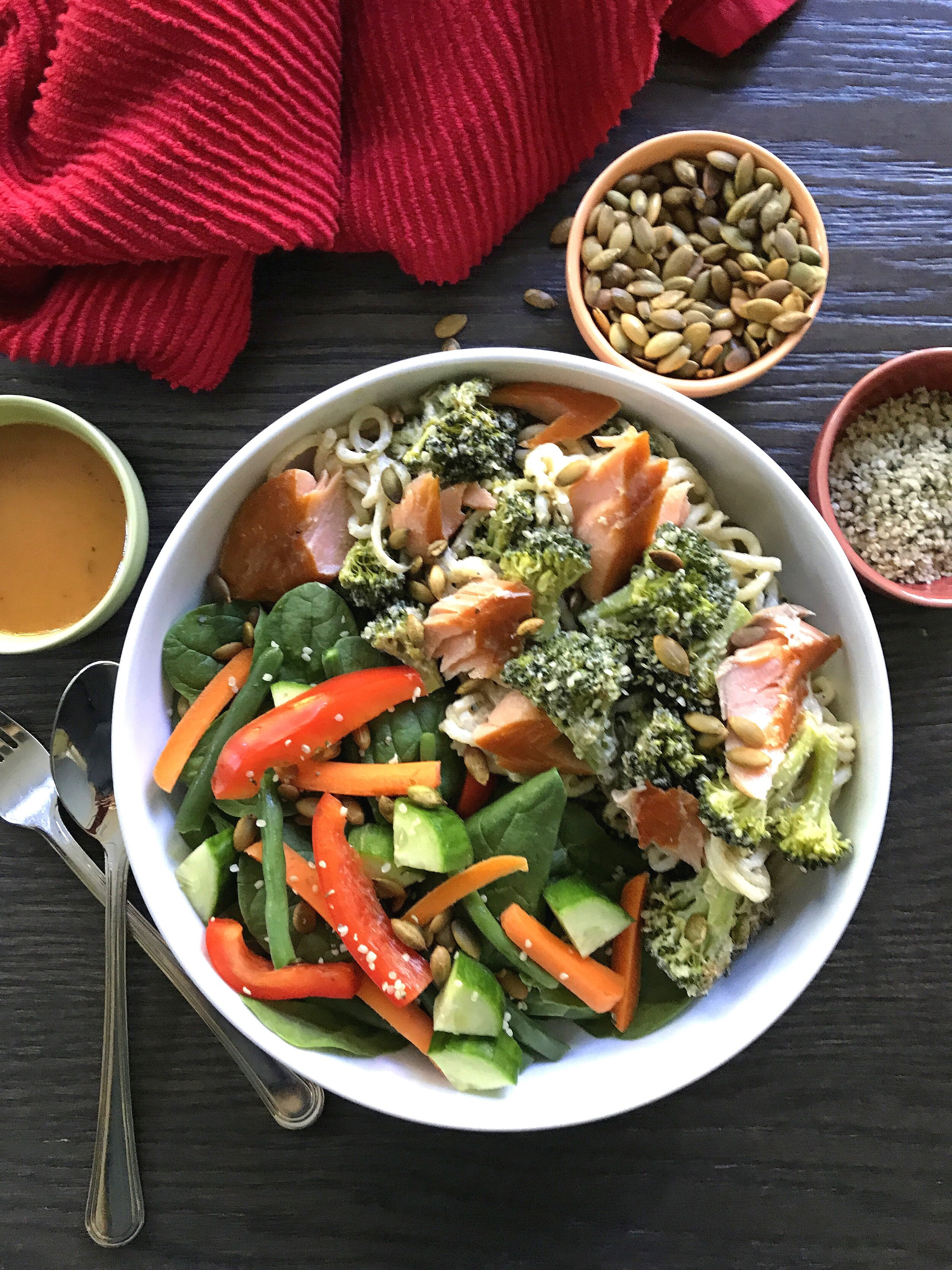 """Dairy-free """"Alfredo"""" Sauce tossed with konjac noodles, roasted broccoli, and smoked trout. Served with a mixed salad, toasted pumpkin seeds, and hemp hearts."""