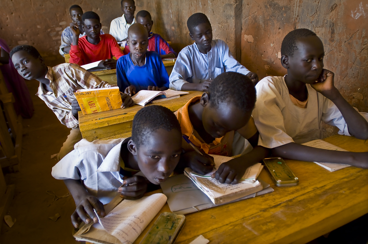 Morning lesson, in Ali Dinnar primary school. Class are mixed, but boys and girls sit in different rows. The curriculum is the sudanese one. 690 pupils attend the school where 19 teachers are working. There are 11 classes for 7 classrooms. There are 6 primary schools in Djabal for 4496 pupils (2420 boys and 2076 girls). 60 % of the camp's population is under 18 years old.