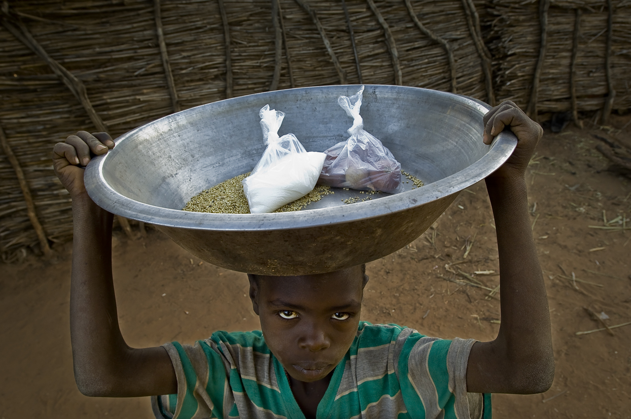 """Ahmed Mahamat Khamis, 8 years old on his way back home from the grocery where he bartered millet for sugar and oignons. He carries in a bucket a bag of sugar, some oignons (in plastic pocket) and the """"change"""": some millet. The barter economy is common practice in the camps. One brings a product to the grocery to get what he lacks (sugar, oignon, soap,...) A koro of mill (measure of a big bowl) is equivalent to 400 CFA (0.85 USD) while a small mould is equivalent to 150 CFA (0.32 USD). Created on 4 june 2004, Djabal camp sheltered 17.766 persons and 4.681 families in december 2011. It is located 4 kilometers west from Goz Beida, 217 kilometers south from Abeche, 900 kilometers east from N'Djamena the capital and 80 kilometers from the sudanese border."""